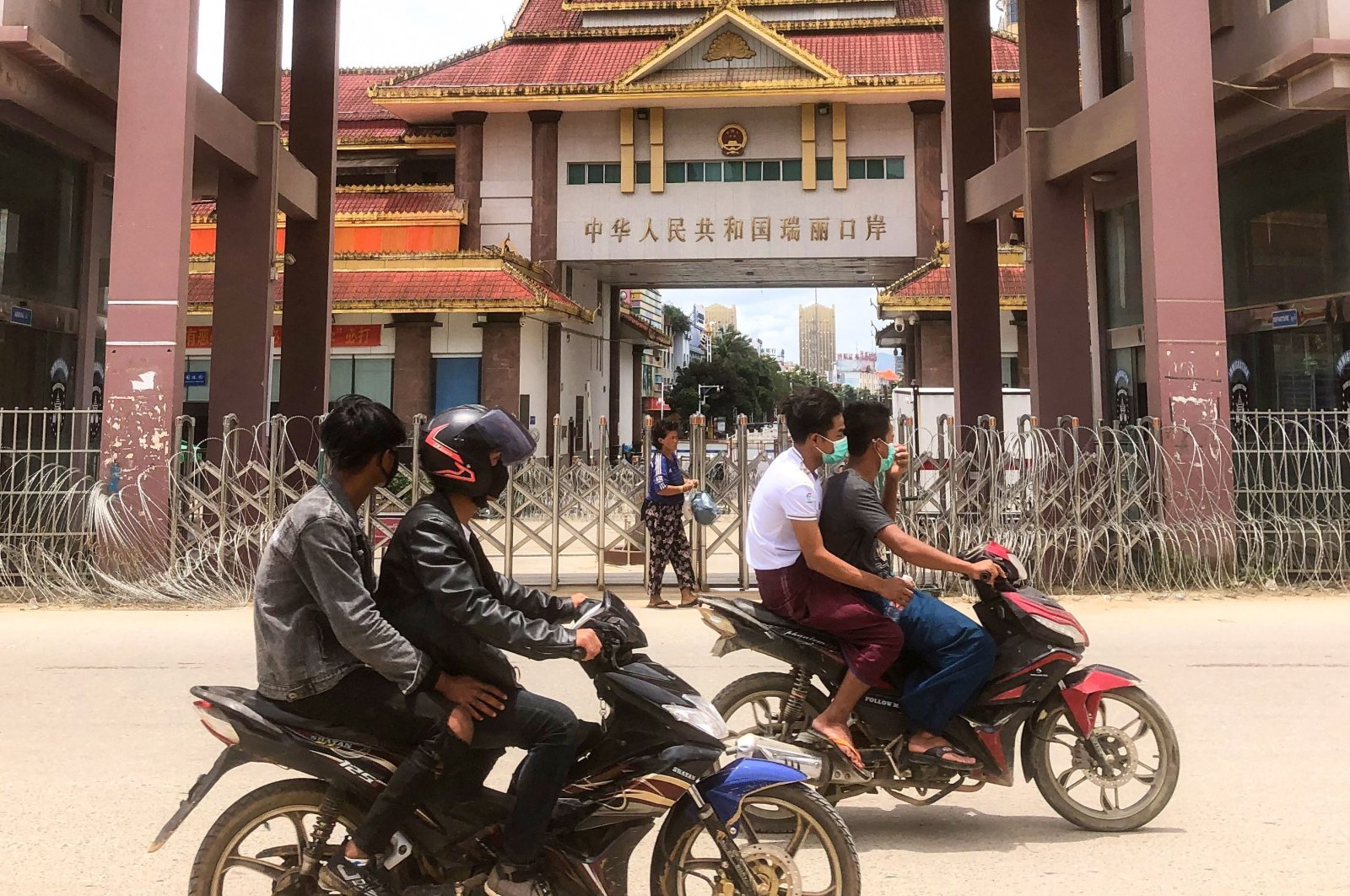 Motorists pass the China-Myanmar border gate in Muse in Shan state, as the Chinese city of Ruili near the border with Myanmar imposed a lockdown and started mass testing after three coronavirus cases were reported, July 5, 2021. (AFP Photo)