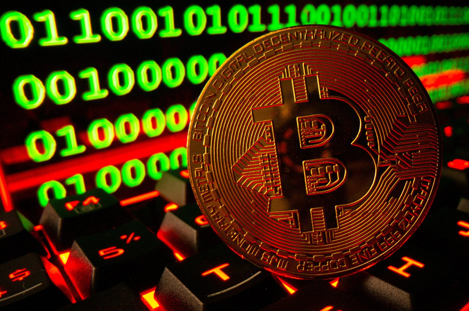 Bitcoin cryptocurrency representation is pictured on a keyboard in front of binary code in this illustration photo taken Sept. 24, 2021. (Reuters Photo)
