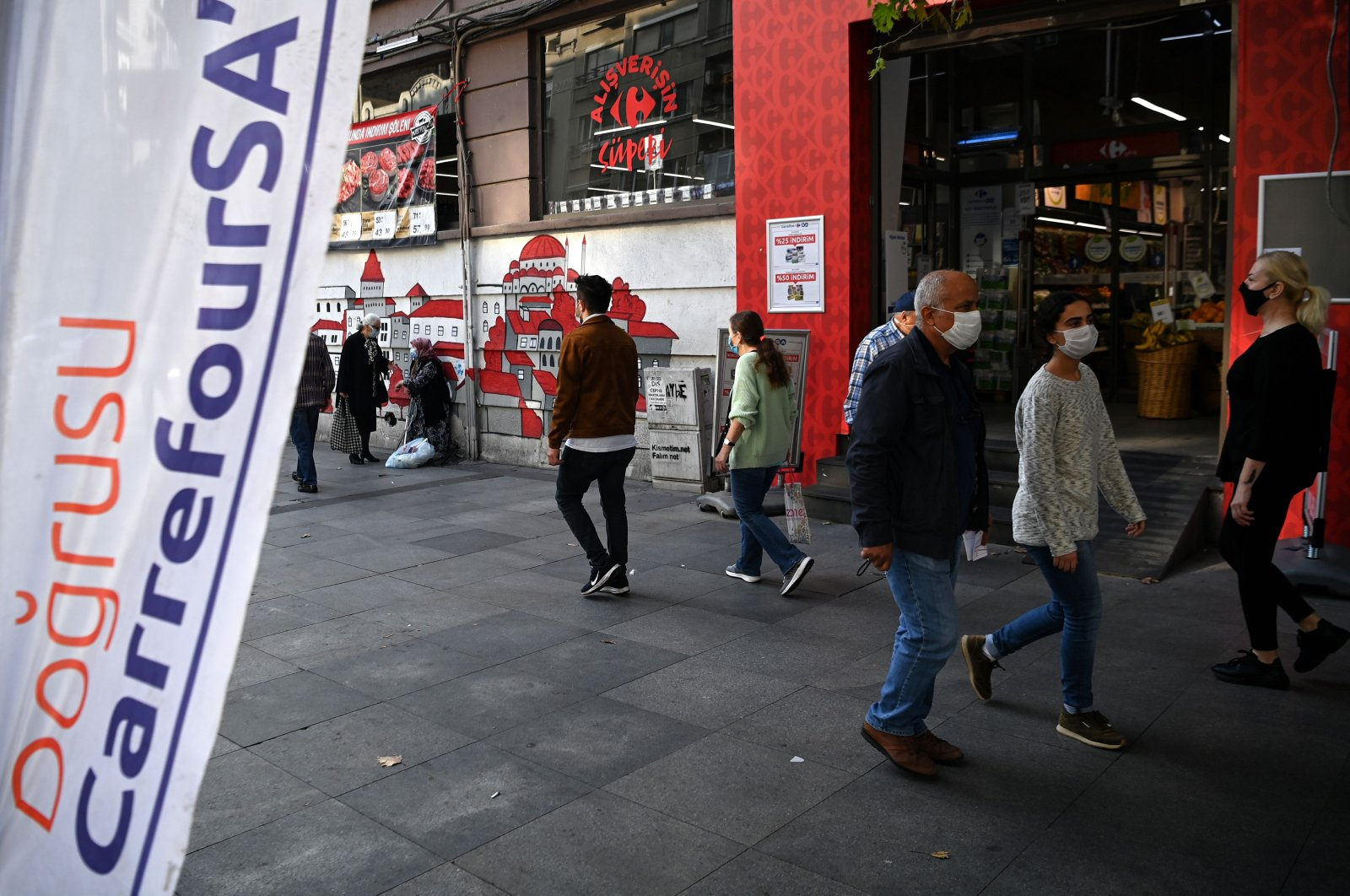 """People wearing face masks walk in front of a French brand supermarket """"Carrefour"""" at Nişantaşı district in Istanbul, Turkey, Oct. 26, 2020. (AFP Photo)"""