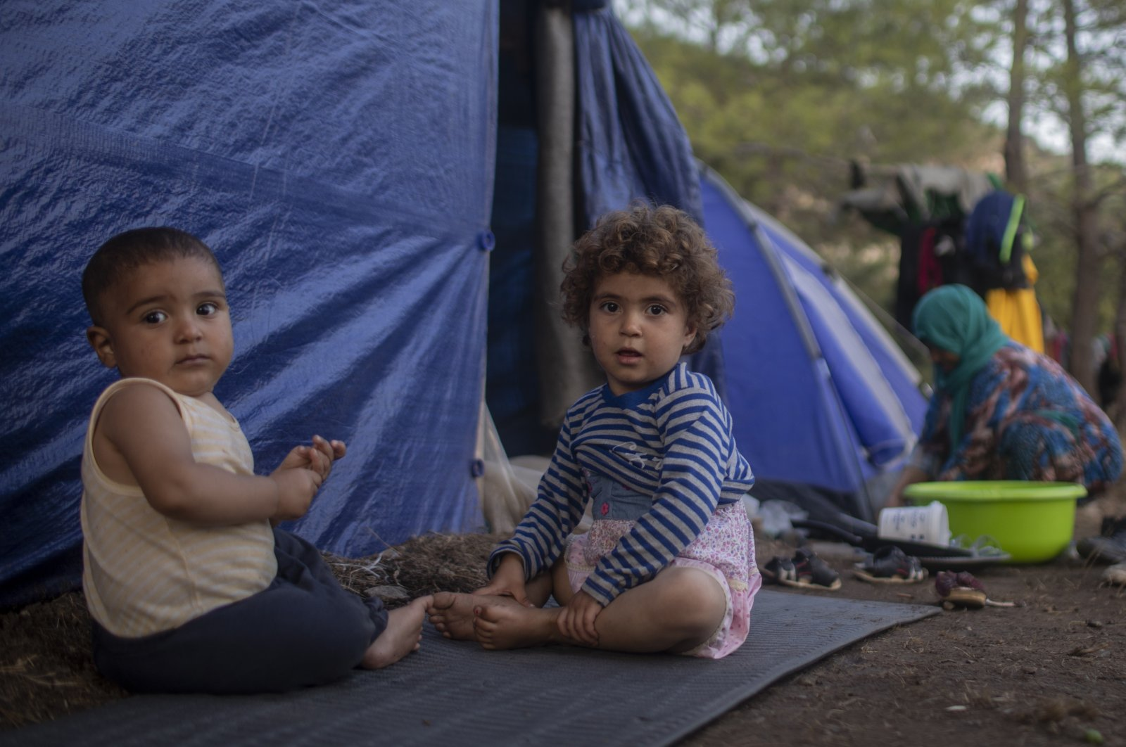 Syrian children play outside a makeshift tent near the refugee and migrant camp on the Greek island of Samos, Sept. 25, 2019. (AP File Photo)