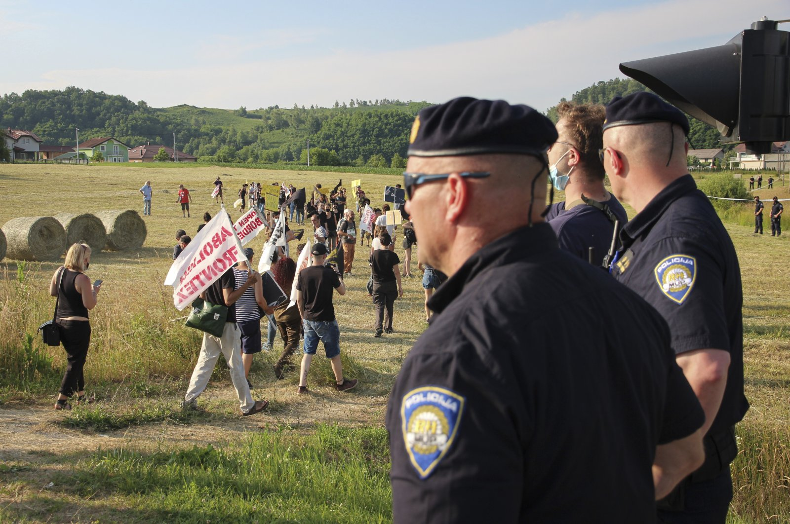 Croatian police officers stand as people walk with banners during a protest against the violent pushbacks of migrants, allegedly conducted by Croatian police, near the border crossing between Croatia and Bosnia Herzegovina in Maljevac, Croatia, June 19, 2021. (AP File Photo)