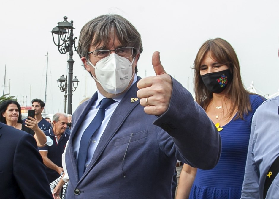 Catalan separatist leader Carles Puigdemont (L) gives thumbs up as he walks with the Speaker of the Catalan Parliament Laura Borras in Alghero, Sardinia, Italy, Saturday, Sept. 25, 2021. (AP Photo)