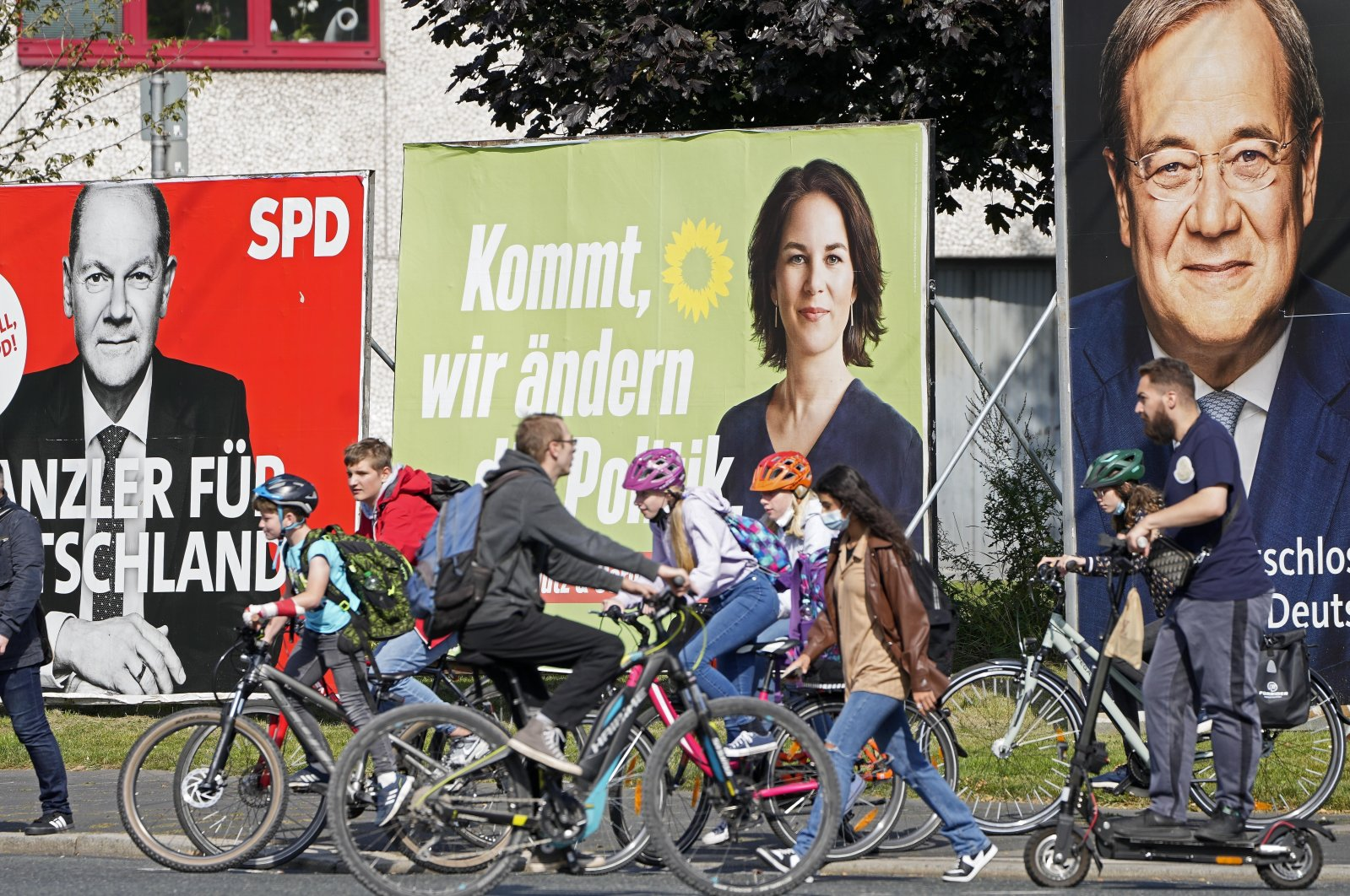 People walk and drive past election posters of the three candidates for German chancellor, Armin Laschet (R), Annalena Baerbock (C) and Olaf Scholz, on a street in Gelsenkirchen, Germany, Sept. 23, 2021. (AP Photo)