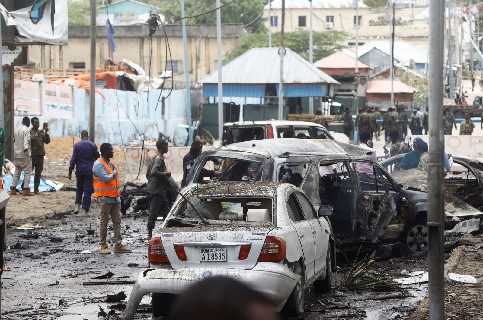 Civilians and Somalian security officers gather at the scene of a suicide car bomb at a street junction near the president's residence, in Mogadishu, Somalia, Sep. 25, 2021. (Reuters Photo)