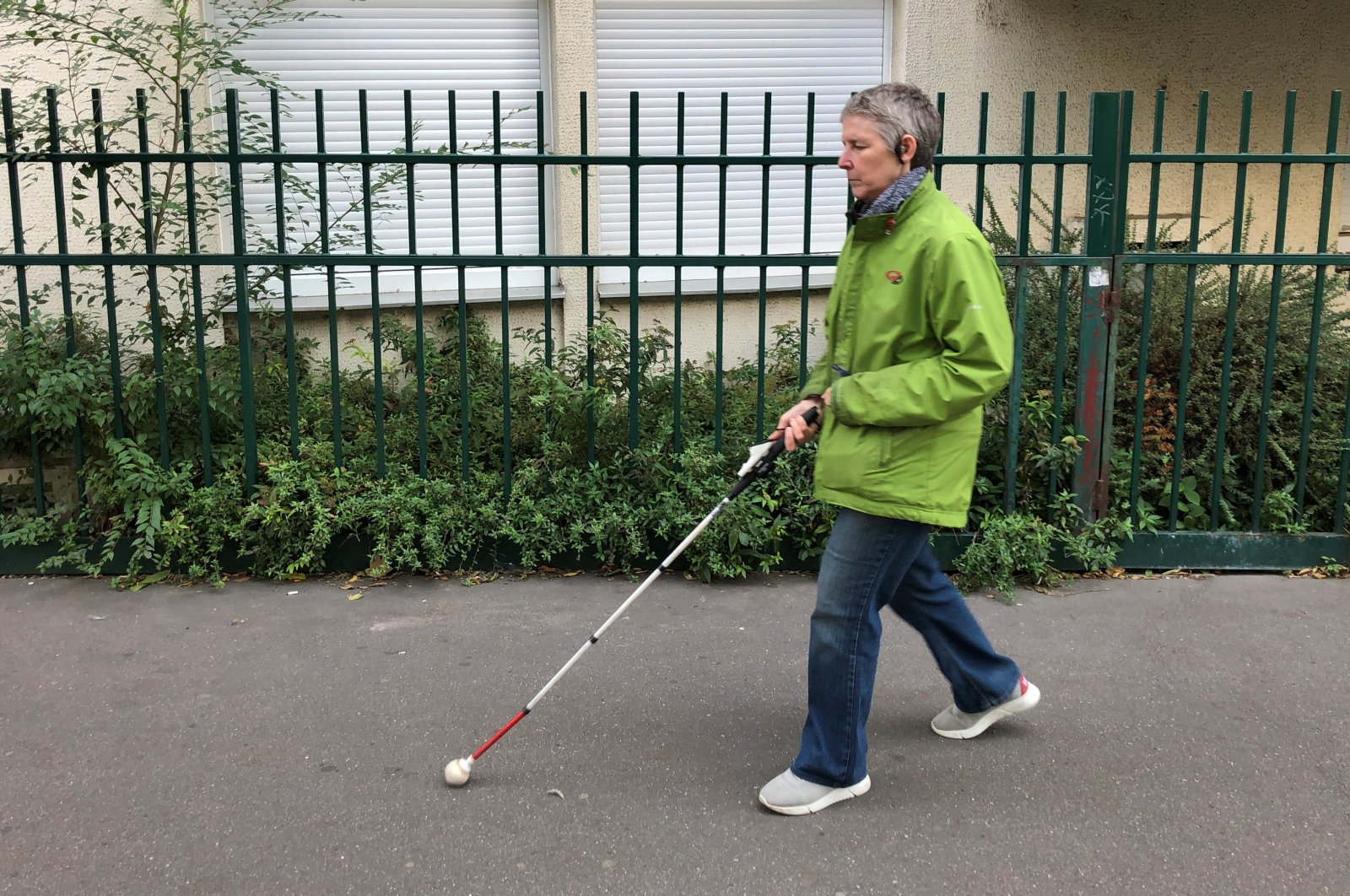 Laurence Jamet, Parisian woman blind since birth, walks with a cane and the electronic device, called Rango, invented by the Lyon-based startup Gosense, which uses sound and augmented reality to warn visually impaired people before a collision can occur, during an interview with Reuters in Paris, France, Sept. 21, 2021. (REUTERS Photo)