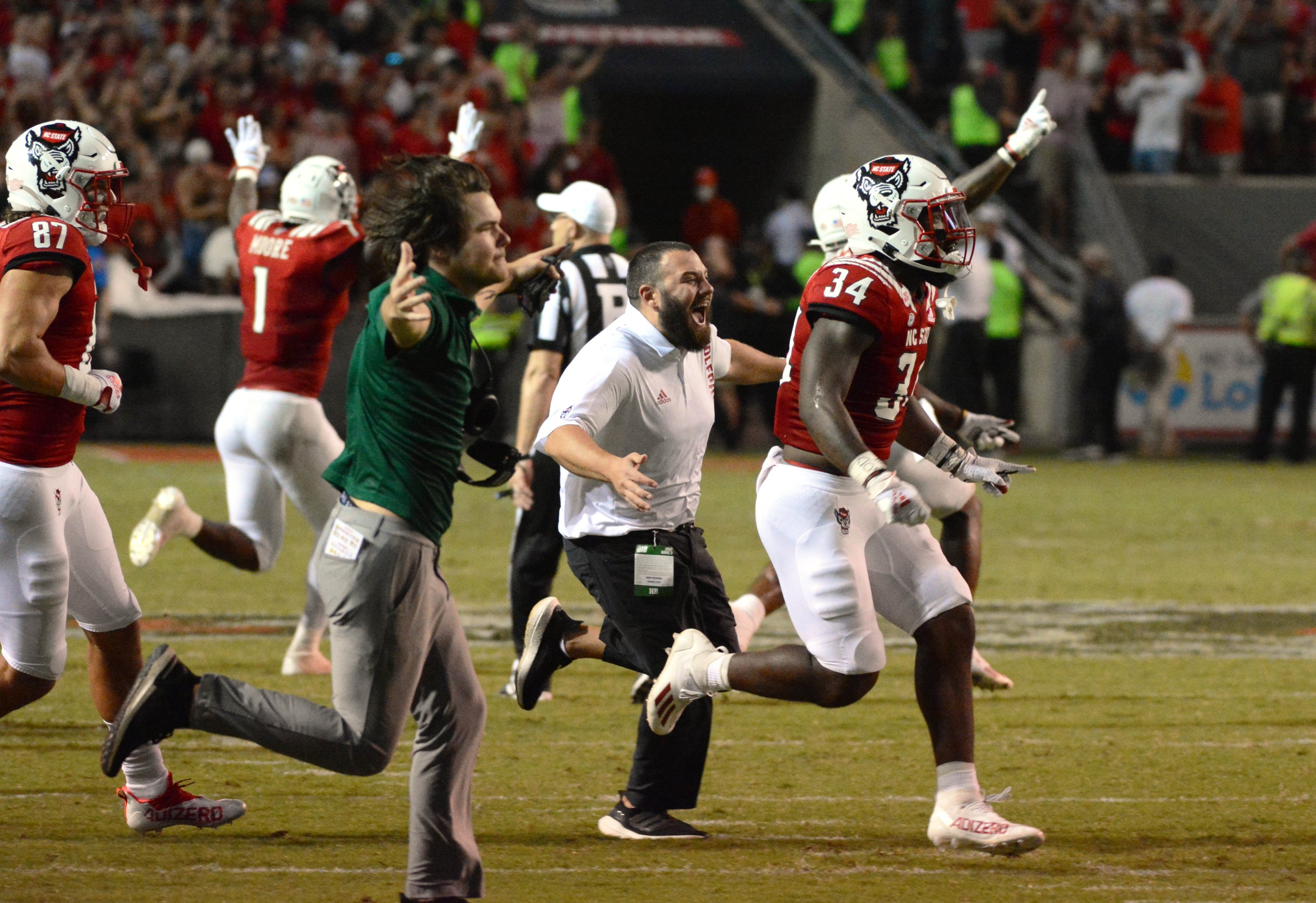 North Carolina State Wolfpack players and coaches celebrate after beating the Clemson Tigers in two overtimes at Carter-Finley Stadium, Raleigh, North Carolina, U.S., Sept. 25, 2021. (Rob Kinnan-USA TODAY Sports via Reuters)