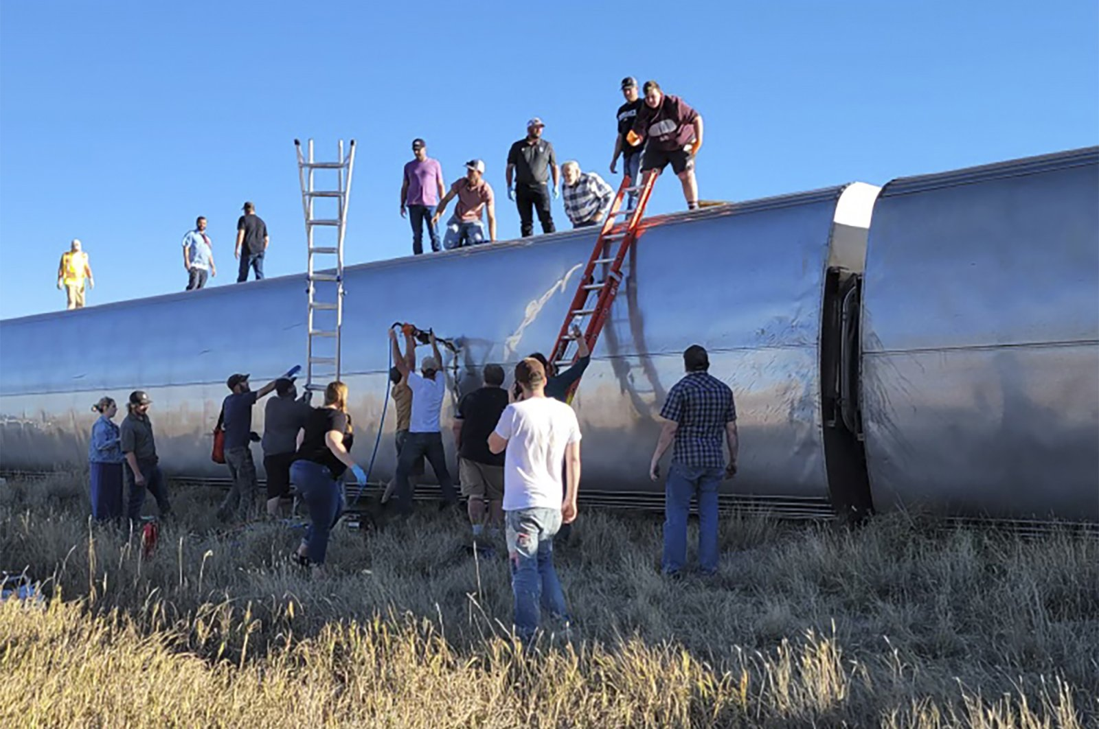 In this photo provided by Kimberly Fossen, people work at the scene of an Amtrak train derailment on Saturday, Sept. 25, 2021, in north-central Montana, U.S. (AP Photo)