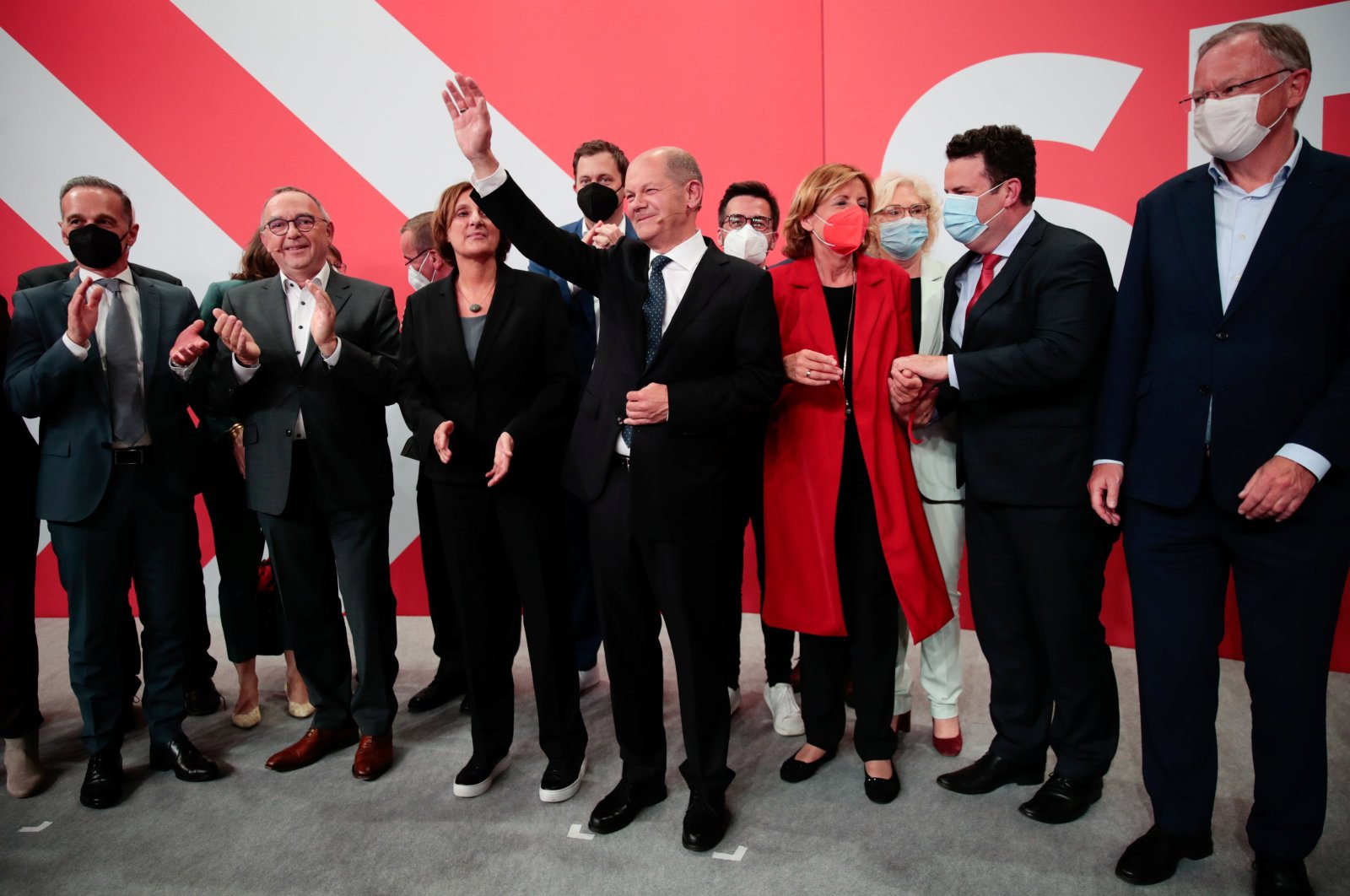 Social Democratic Party (SPD) leader and top candidate for chancellor Olaf Scholz (C), his wife Britta Ernst (C-R), German Labor Minister Hubertus Heil  (2nd R), Rhineland-Palatinate State Premier Malu Dreyer (C-L), Social Democratic Party (SPD) secretary-general Lars Klingbeil (rear C), German Foreign Minister Heiko Maas, and Lower Saxony's State Premier Stephan Weil (far right) react after first exit polls for the general elections in Berlin, Germany, Sept. 26, 2021. (Reuters Photo)