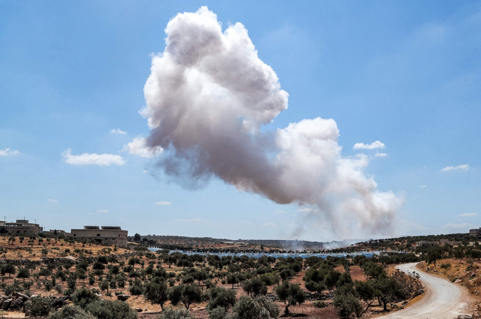 A smoke plume rises after an aerial bombardment near a make-shift camp for displaced Syrians near the town of Kafraya, north of Syria's Idlib province, Syria, Sept. 7, 2021. (AFP Photo)