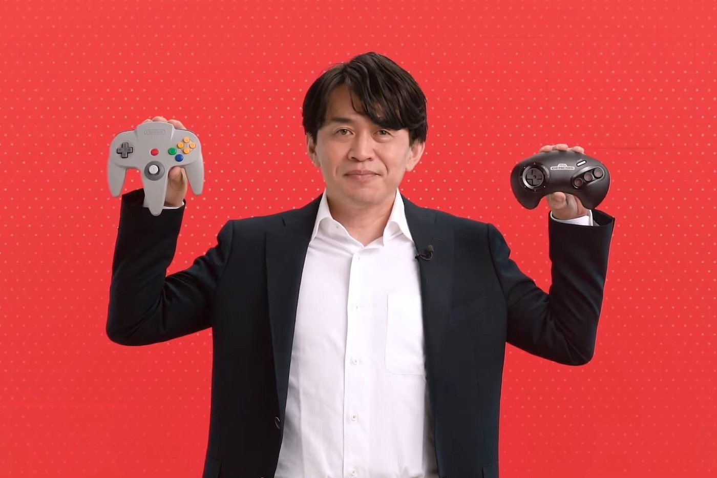 A Nintendo executive shows the new Nintendo 64 (L) and Sega Genesis controllers in this promotional photo released by Nintendo (Credit: Nintendo)
