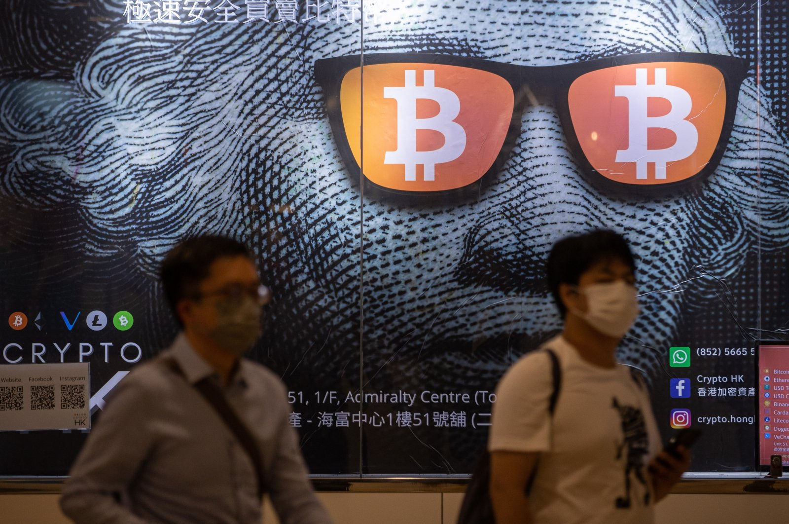 Two men walk past an advertising poster for bitcoins and cryptocurrencies in Hong Kong, China, Sept. 25, 2021. (EPA Photo)