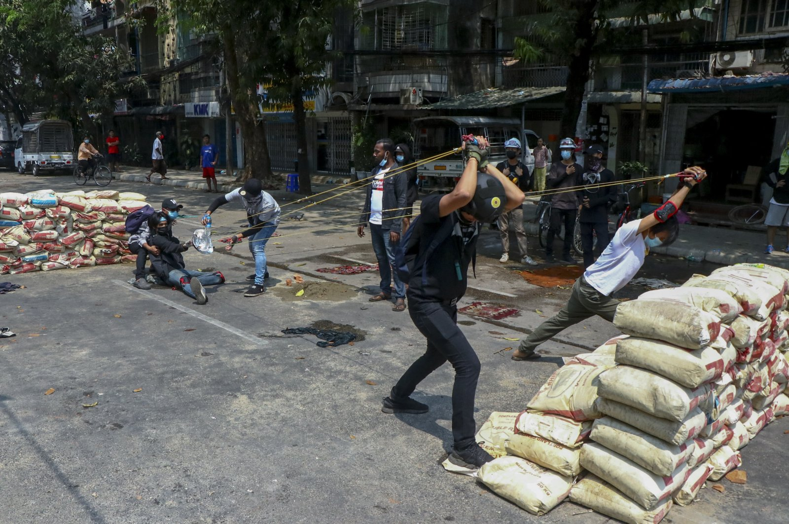 Anti-coup protesters test an improvised weapon they made to fight with armed Myanmar security forces in Yangon, Myanmar, March 17, 2021. (AP Photo)