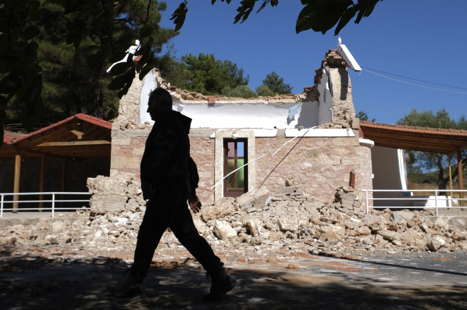 A Resident passes next to a damaged Greek Orthodox chapel after a strong earthquake in Arcalochori village on the southern island of Crete, Greece, Sept. 27, 2021. (AP Photo)