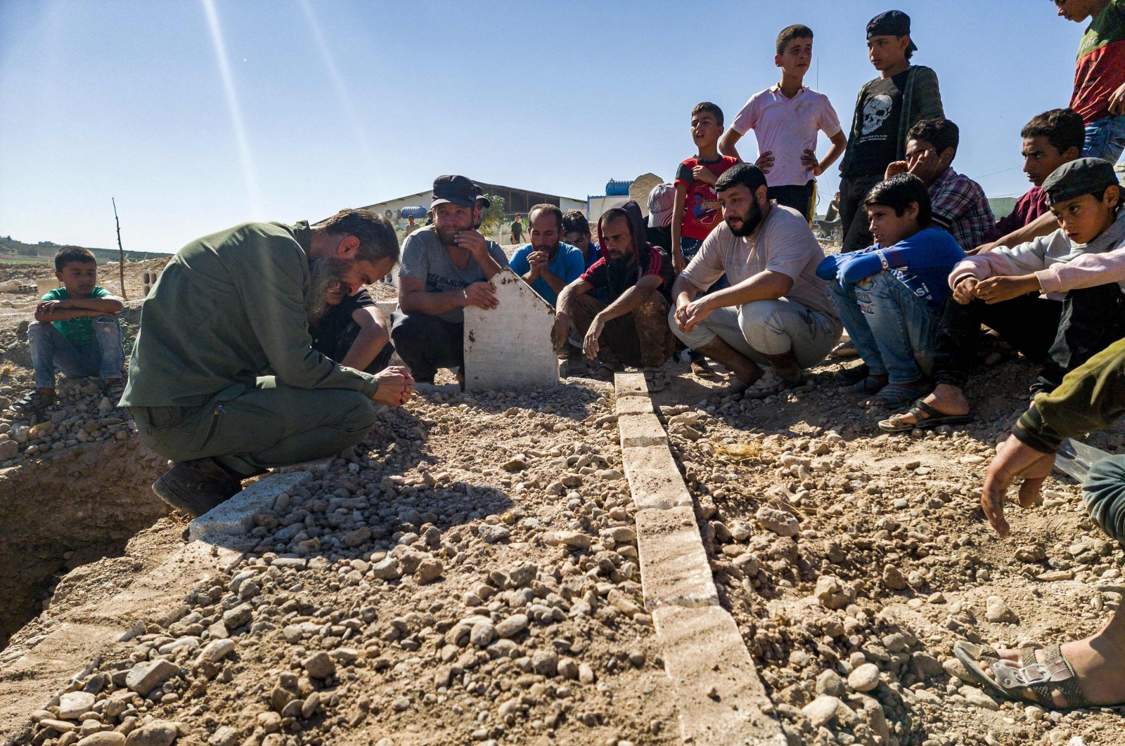 """Mourners gather by the grave of one of fighters from the """"Hamza Division"""" Syrian opposition group killed in Russian air raids in the countryside of Aleppo in the Afrin region of northwestern Syria, Sept. 26, 2021. (AFP Photo)"""