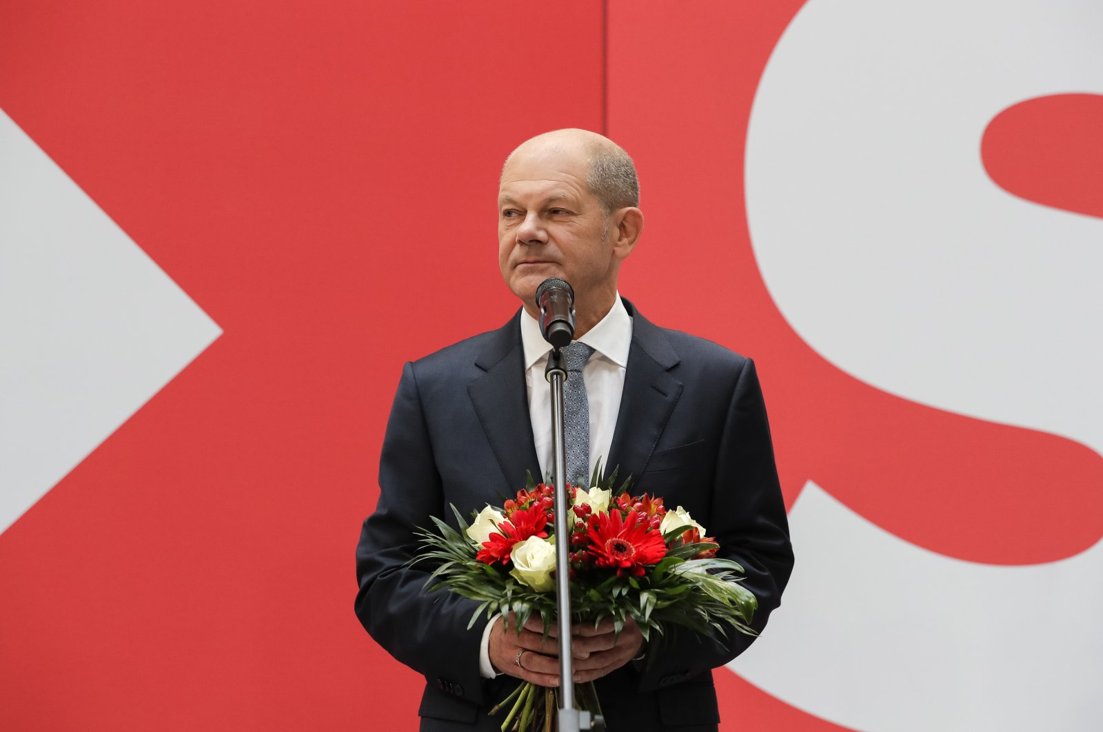 Olaf Scholz, the top candidate for chancellor of the Social Democratic Party (SPD), holds a bunch of flowers during a press statement at the party's headquarters in Berlin, Germany, Sept. 27, 2021. (AP Photo)