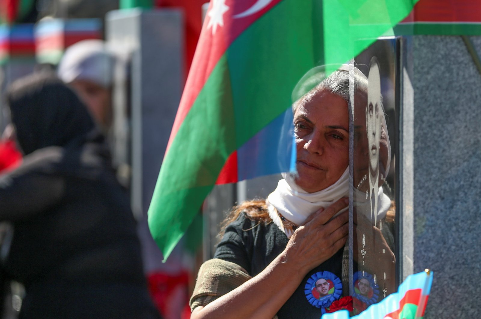A woman grieves at a cemetery during commemorations for Azerbaijani service members killed in the conflict over the region of Nagorno-Karabakh on its first anniversary, in Baku, Azerbaijan, Sept. 27, 2021. (Reuters Photo)