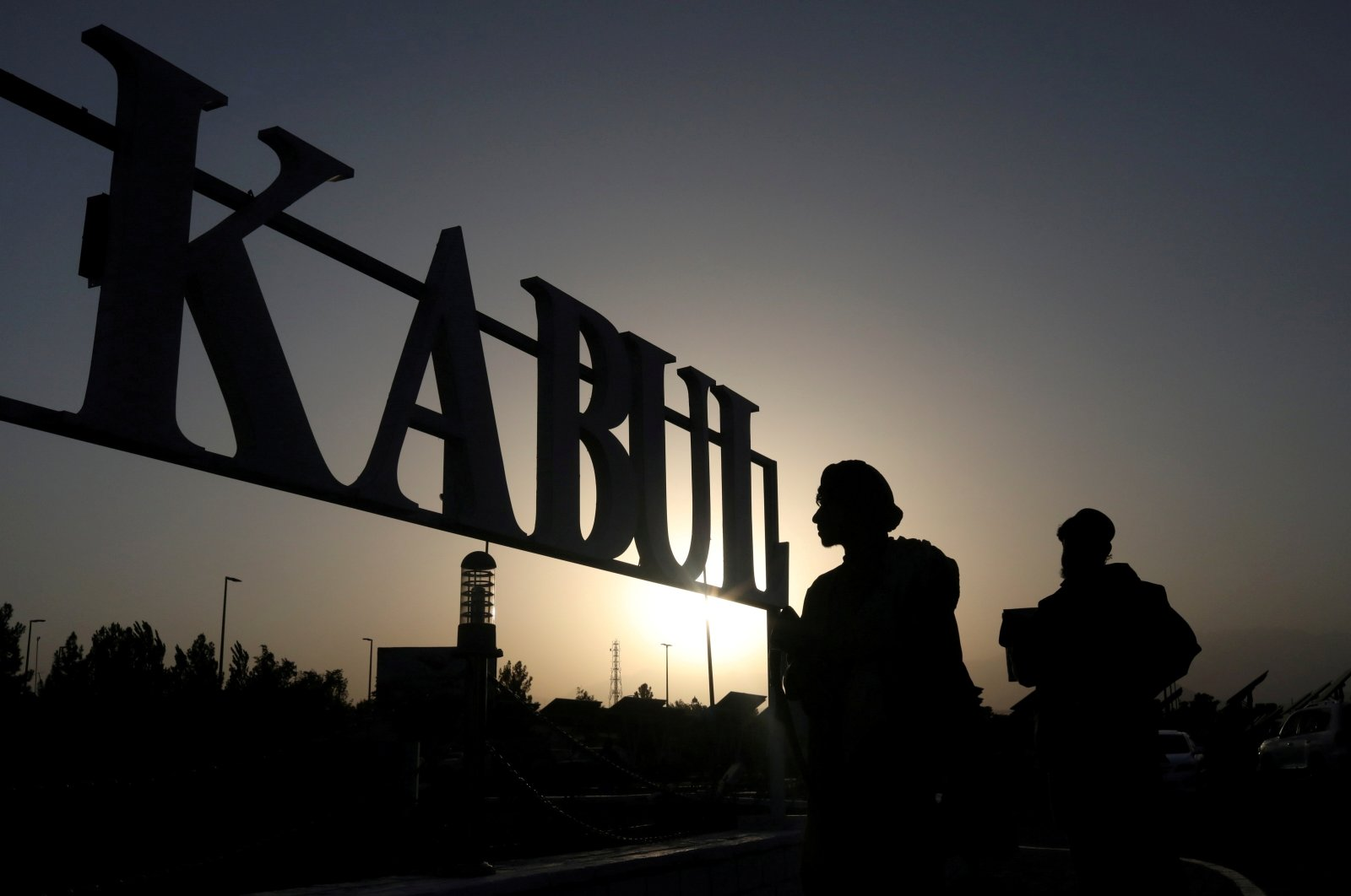 Taliban soldiers stand in front of a sign at Kabul Hamid Karzai International Airport  in Kabul, Afghanistan, Sept. 9, 2021. (REUTERS Photo)