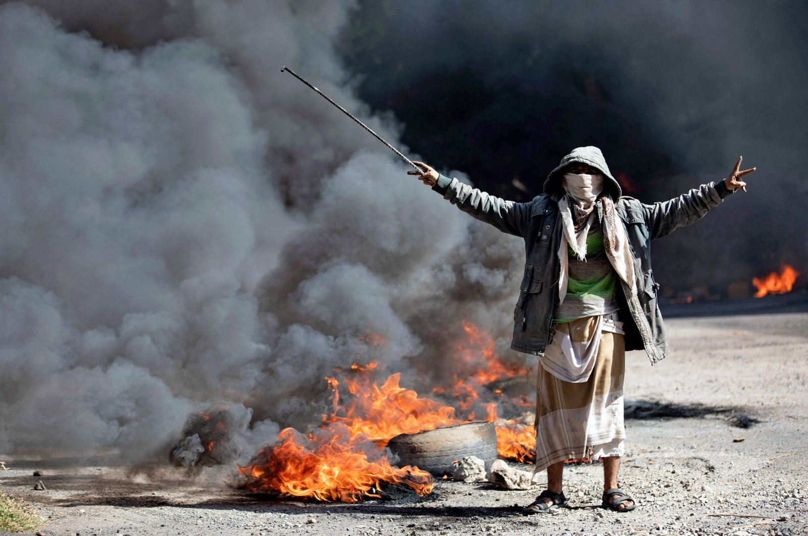 A Yemeni man flashes the V for victory sign next to burning tires during protests calling for the removal of the Saudi-backed coalition government and deteriorating economic and living conditions, in Yemen's third city of Taez on Sept. 27, 2021. (AFP Photo)