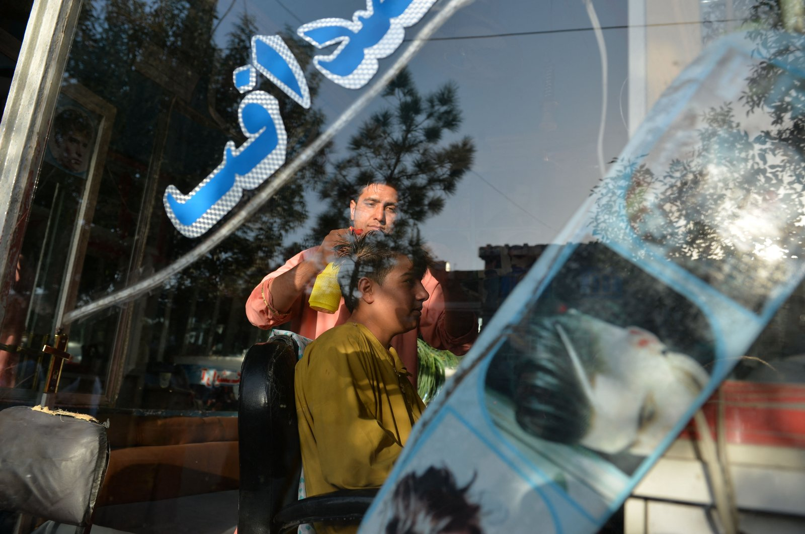 Nader Shah (L) attends a customer at his barbershop in Herat, Sept. 19, 2021. (AFP Photo)