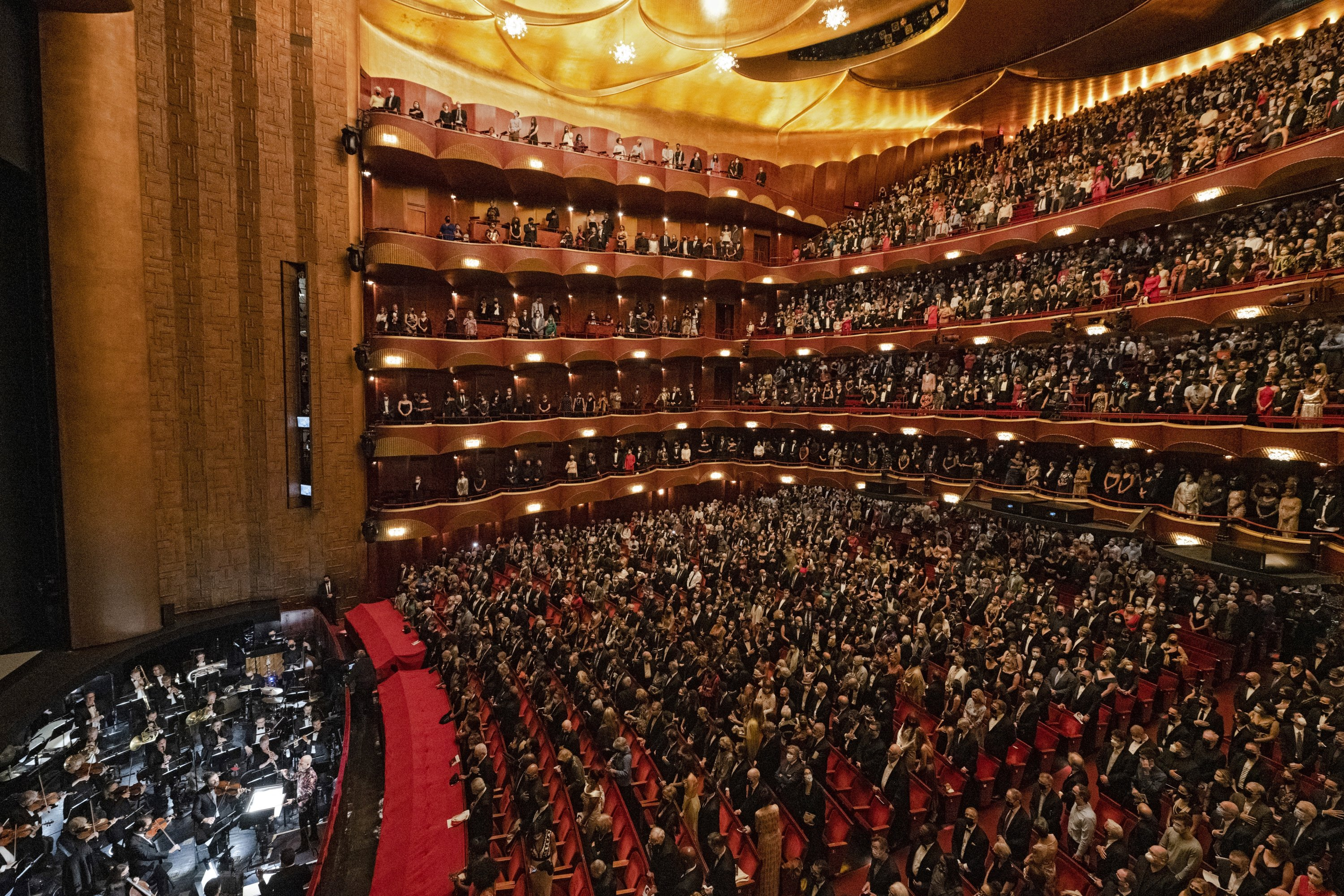 In this photo provided by the Metropolitan Opera, the audience stands for the national anthem before the performance of Terence Blanchard's 'Fire Shut Up in My Bones,' which opened the Metropolitan Opera's 2021-2022 season on Monday, Sept. 27, 2021, in New York. (Jonathan Tichler/Metropolitan Opera via AP)