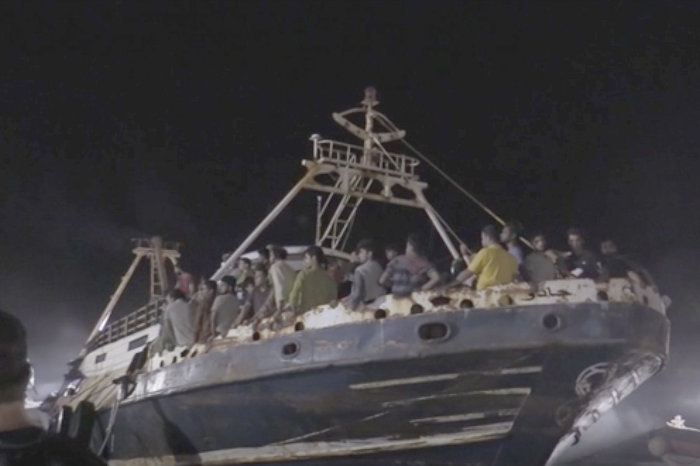 In this frame taken from video, a fishing boat with migrants is docked at the port of the Sicilian island of Lampedusa, southern Italy, Sept. 27, 2021. (AP Photo)