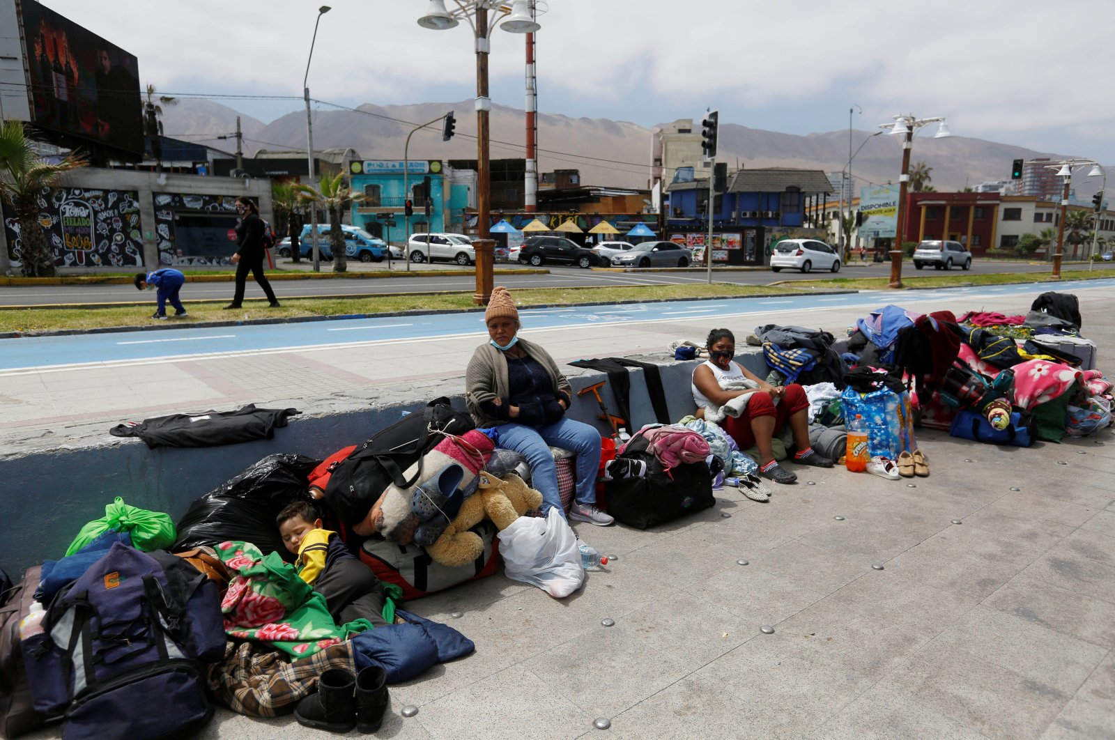 Venezuelan migrants sit along a street next to the ocean after their camp was destroyed during violent anti-immigration protests, in Iquique, Chile, September 27, 2021. (Reuters Photo)