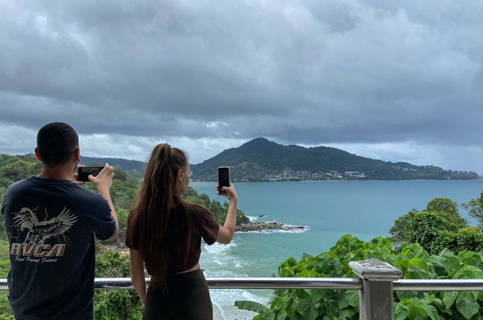 Tourists use their mobile phones to take pictures of the view from Laem Sing viewpoint in Phuket, Thailand, Sep. 21, 2021. (AFP Photo)