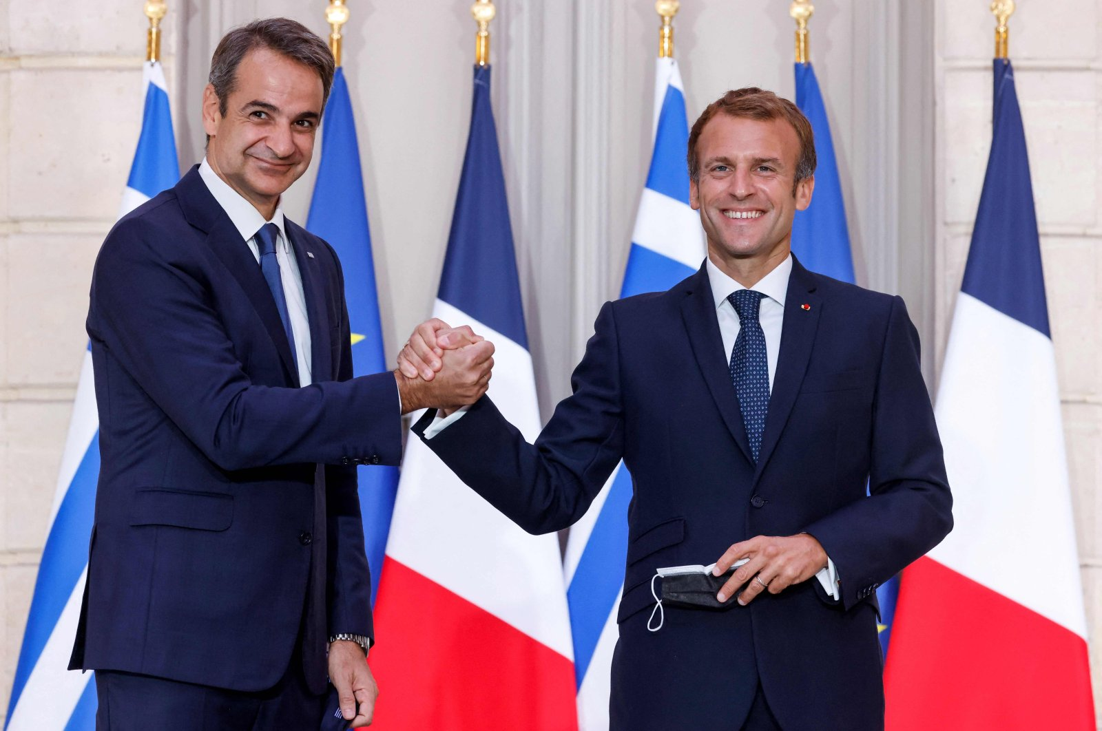 Greek Prime Minister Kyriakos Mitsotakis (L), shakes hands with French President Emmanuel Macron following a signing ceremony of a new defense deal at The Elysee Palace, Paris, France, September 28, 2021. (AFP Photo)