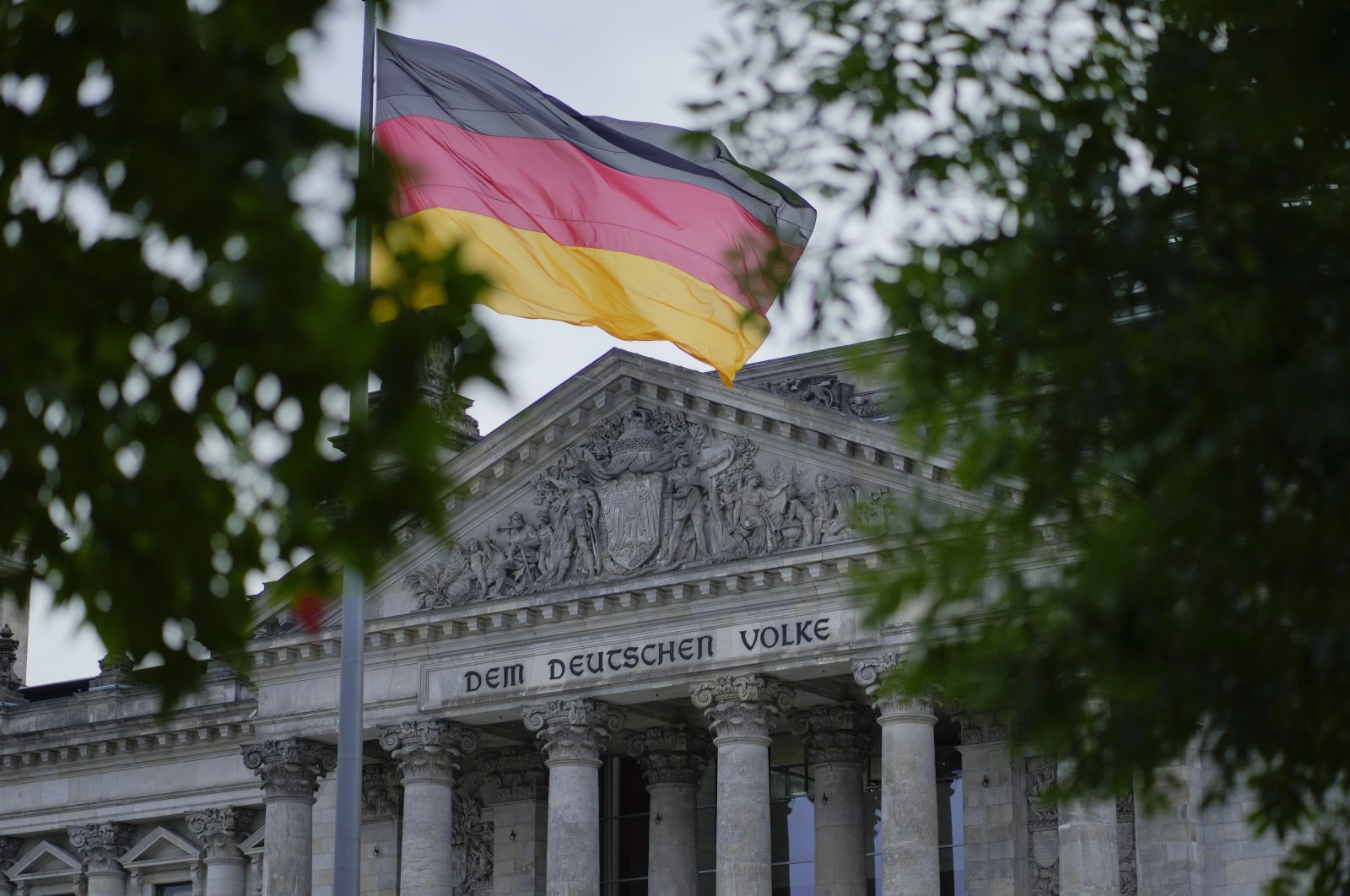 """The German national flag waves in front of the German parliament building, the Reichstag Building, with the slogan """"To The German People,"""" in Berlin, Germany, Sept. 28, 2021. (AP Photo)"""