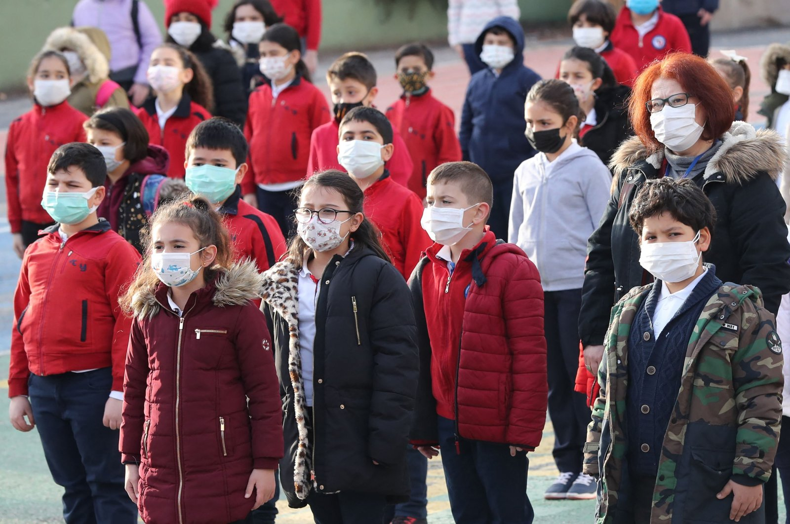 Pupils wearing protective facemasks stand in the courtyard of a school in Ankara on March 2, 2021, after the country lifted restriction measures against the COVID-19 pandemic in regions with lower infection rates. (AFP Photo)