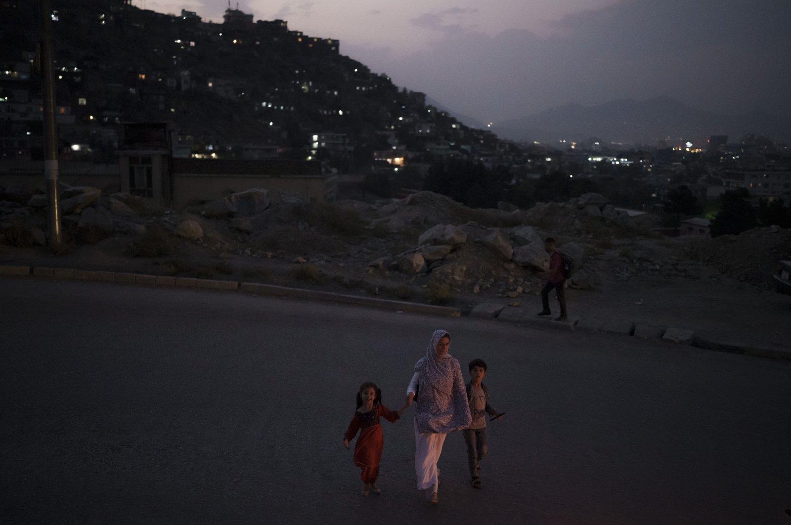 An Afghan family crosses a street at dusk in Kabul, Afghanistan, Sunday, Sept. 19, 2021. (AP Photo/Felipe Dana)