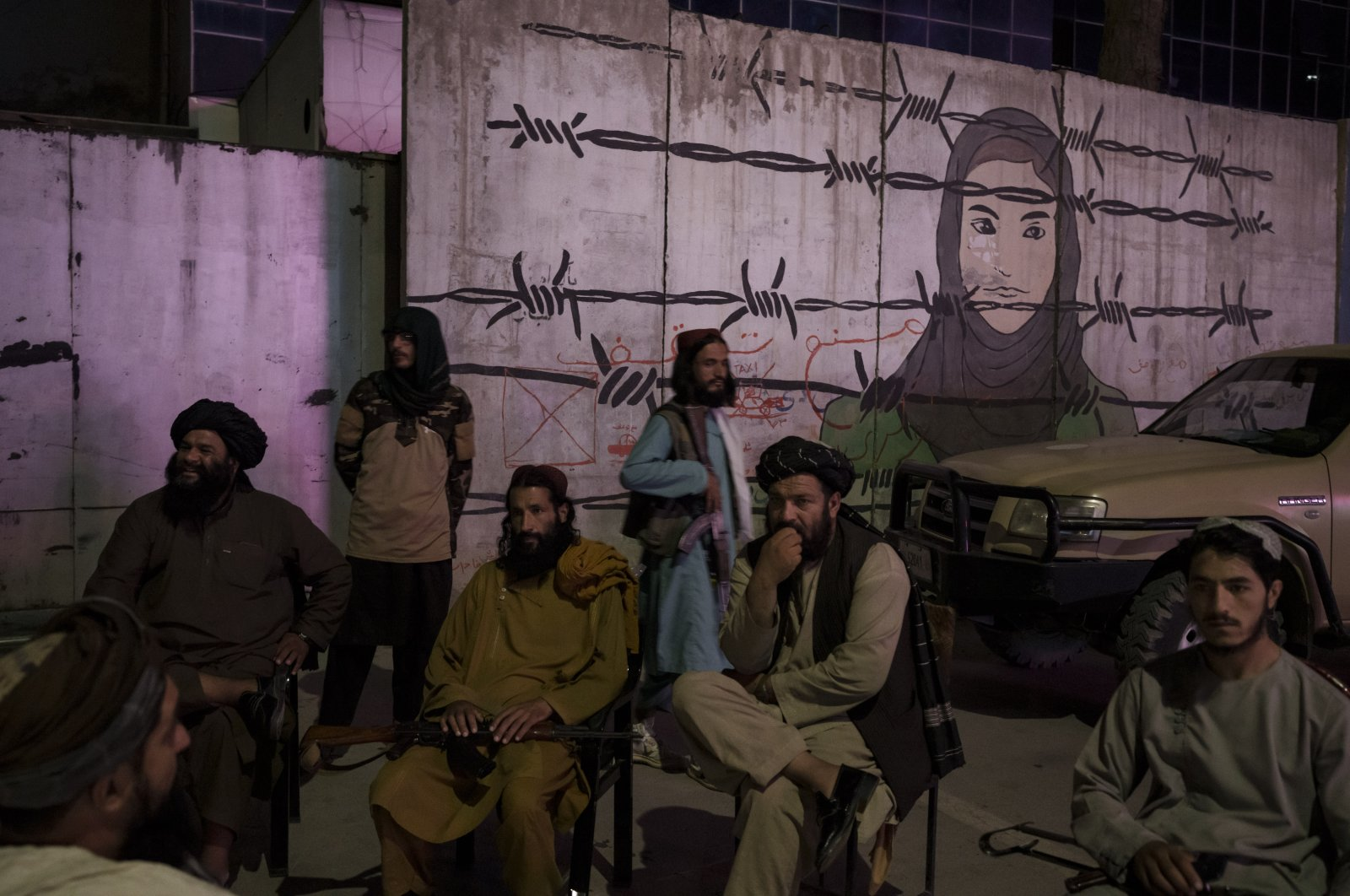 Taliban members sit in front of a mural depicting a woman behind barbed wire in Kabul, Afghanistan, Sept. 21, 2021. (AP Photo)