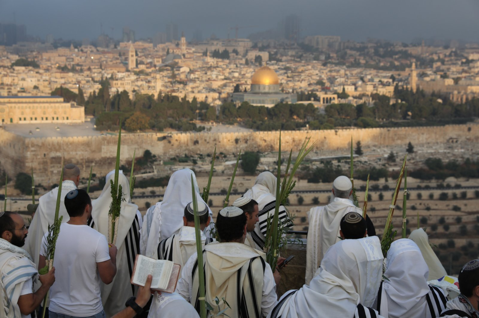 """Orthodox Jews wearing prayer shawls and carrying the """"four species"""" (the four plants that are mentioned in the Torah as being relevant to Sukkot) pray during a special prayer called """"Hoshana Raba"""" as part of the celebration of the seventh day of Sukkot, the Feast of the Tabernacles, in the Mount of Olives with a view of the Old City of Jerusalem, Israel, Sept. 27, 2021. (EPA Photo)"""