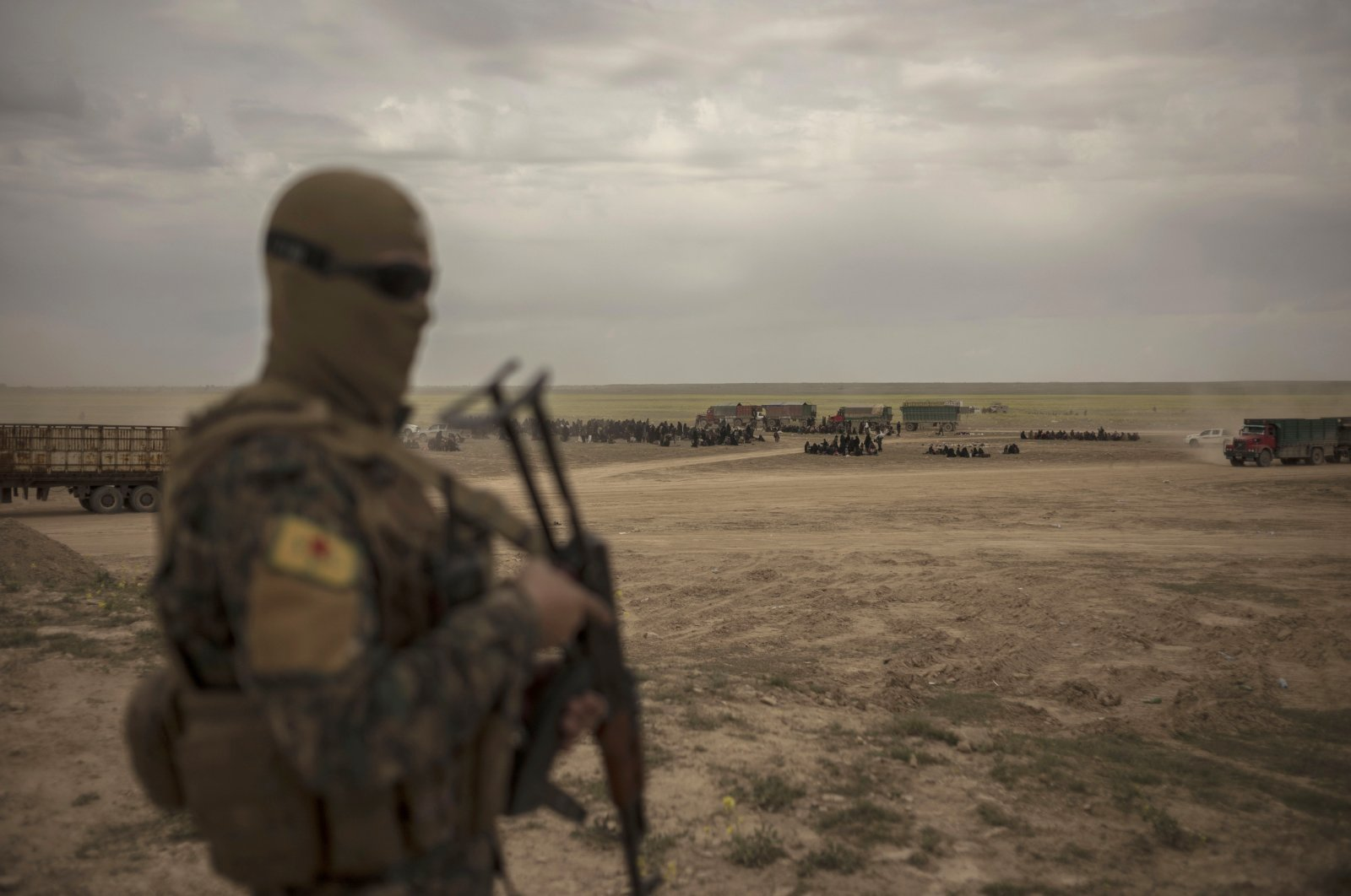 A YPG terrorist stands guard, outside Baghouz, Syria. (AP File Photo)
