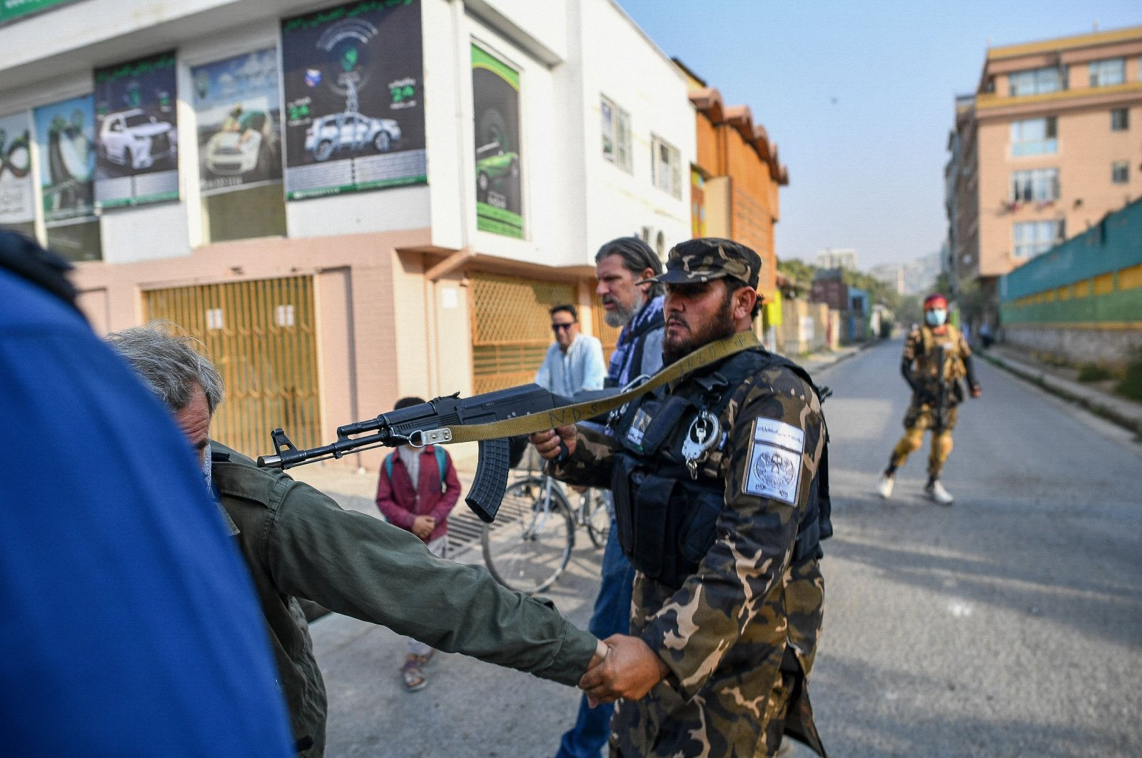 A member of the Taliban special forces pushes a journalist (L) while covering a demonstration by female protestors outside a school in Kabul, Afghanistan, on Sept. 30, 2021. (AFP Photo)