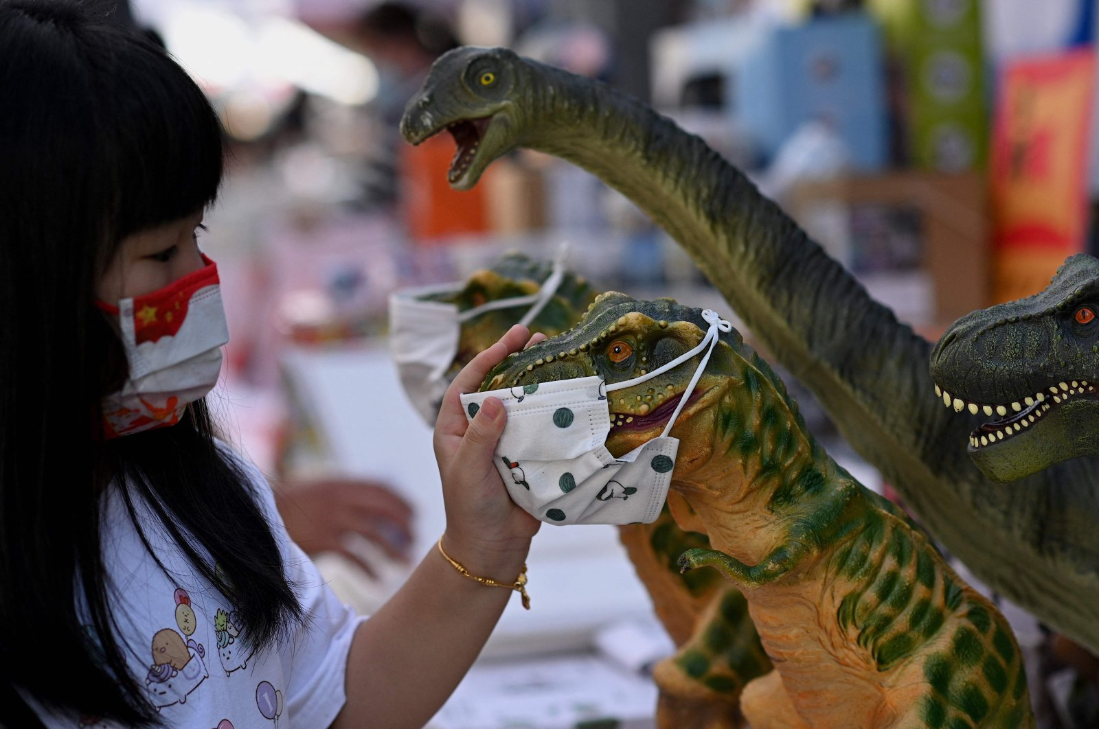 A girl looks at toy dinosaurs with face masks in Qianmen street in Beijing, China, Sept. 21, 2021. (AFP Photo)