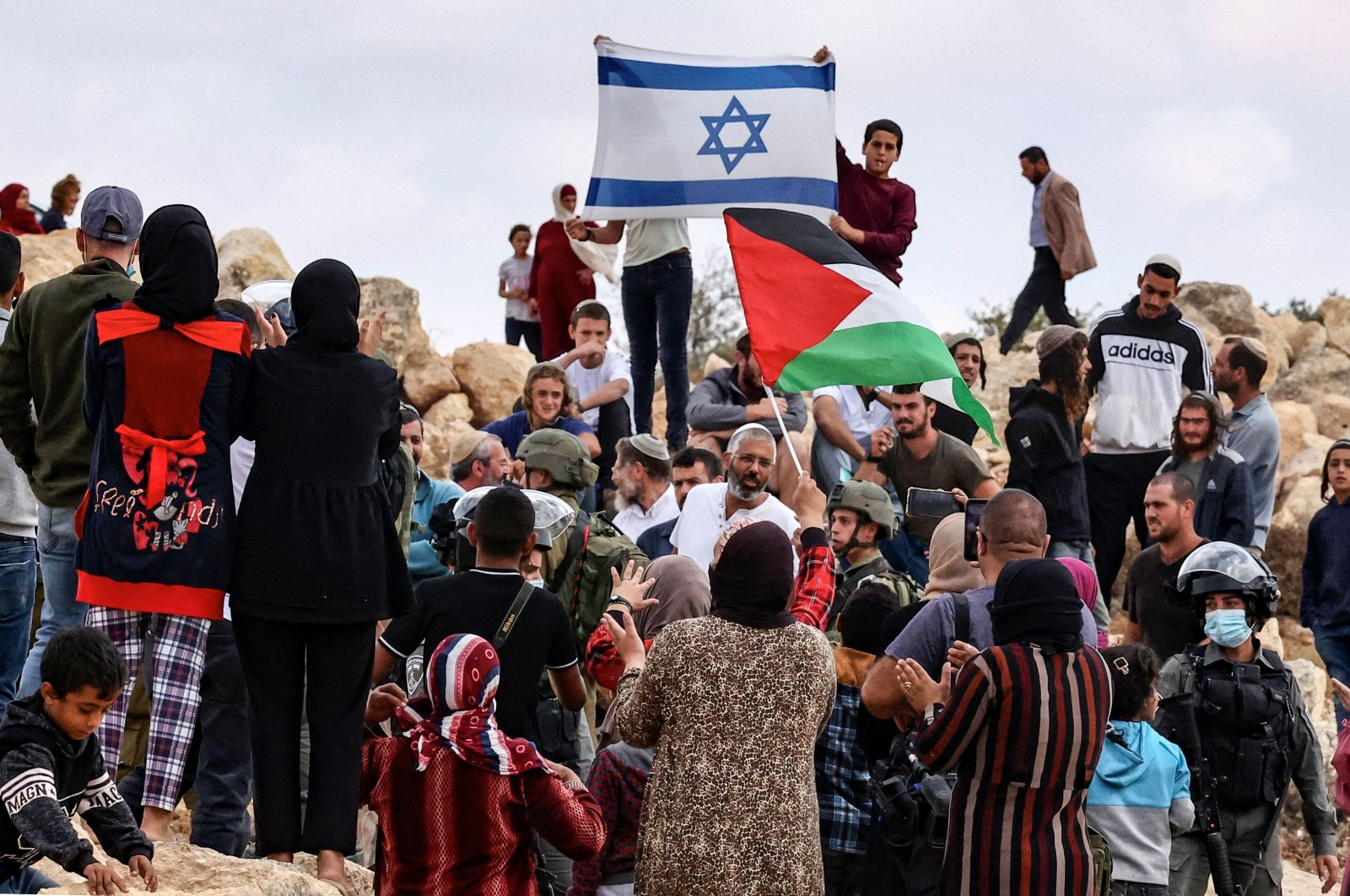 Palestinians from the village of Susya confront Jewish settlers from the settlement of the same name, as both sides raise their national flags, during the visit of representatives of the European Union to the area C (under Israeli administration) of the West Bank, on the outskirts of the village of Yatta, on Sept. 24, 2021. (AFP Photo)