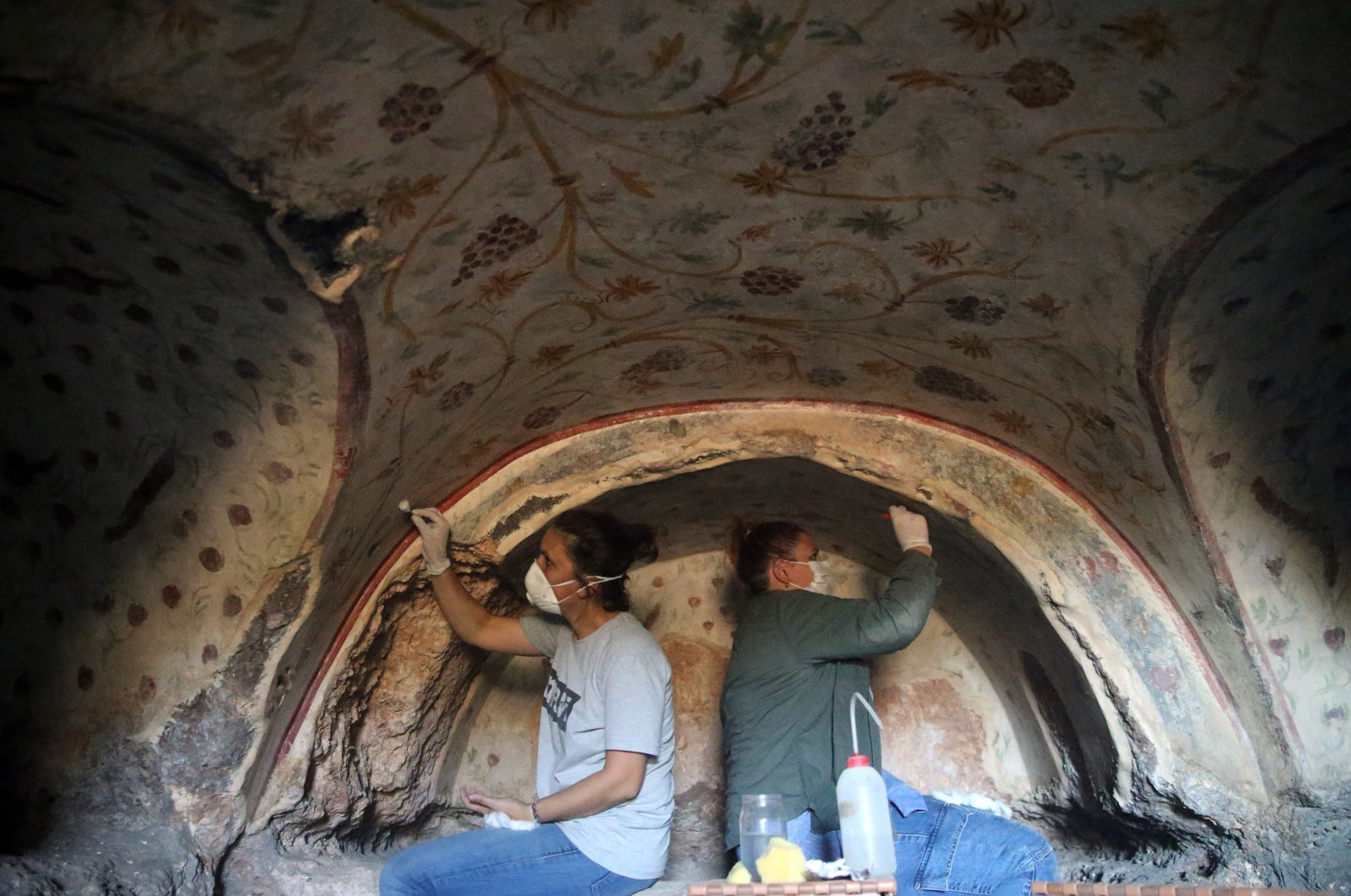 Two archaeologists work on the wall motifs of a room inside a rock tomb in the ancient city ofBlaundus, Uşak, western Turkey, Sept. 29, 2021. (AA Photo)