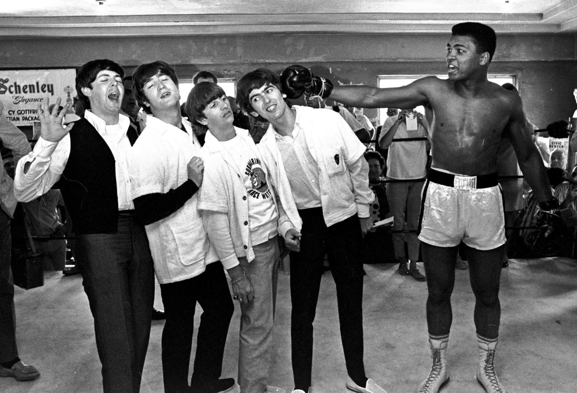 The Beatles, from left, Paul McCartney, John Lennon, Ringo Starr, and George Harrison, take a fake blow from Muhammad Ali, while visiting the heavyweight contender at his training camp in Miami Beach, Florida, Feb. 18, 1964. (AP Photo)