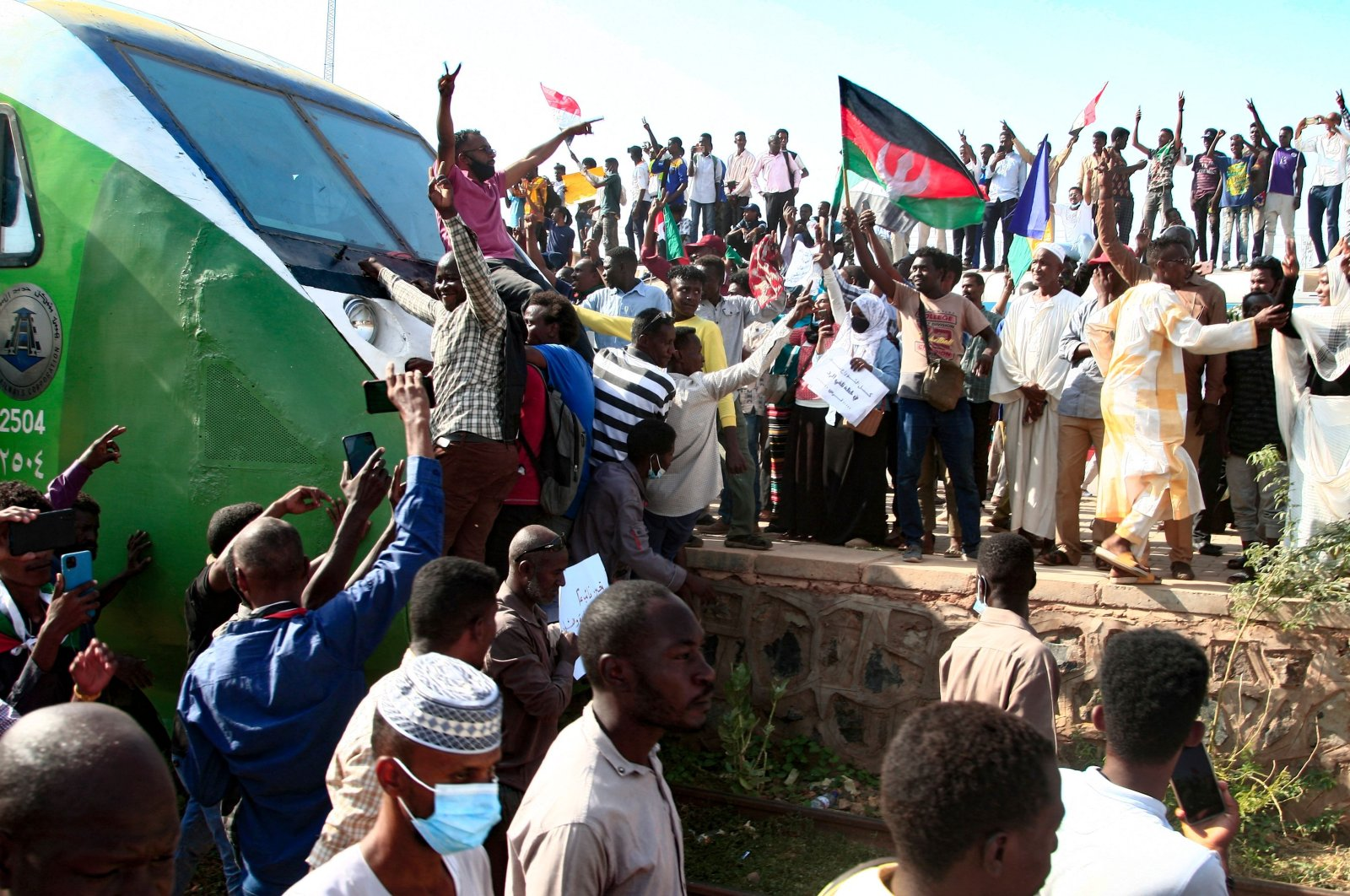 Sudanese protesters cheer as they greet fellow demonstrators upon their arrival on a train from Madani, the capital of Sudan's east-central al-Jazirah state, to join a rally in support of a civilian-led transition to democracy, Sept. 30, 2021. (AFP Photo)