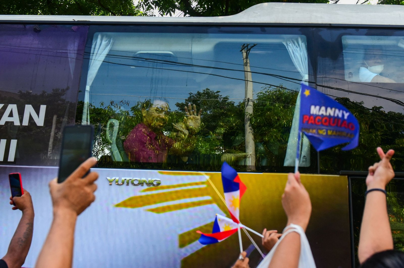 Philippine boxing icon and senator Manny Pacquiao waves to supporters as he arrives in a bus to file his certicate of candidacy for the Philippine presidency in Manila on Oct. 1, 2021. (Photo by Maria Tan / AFP)