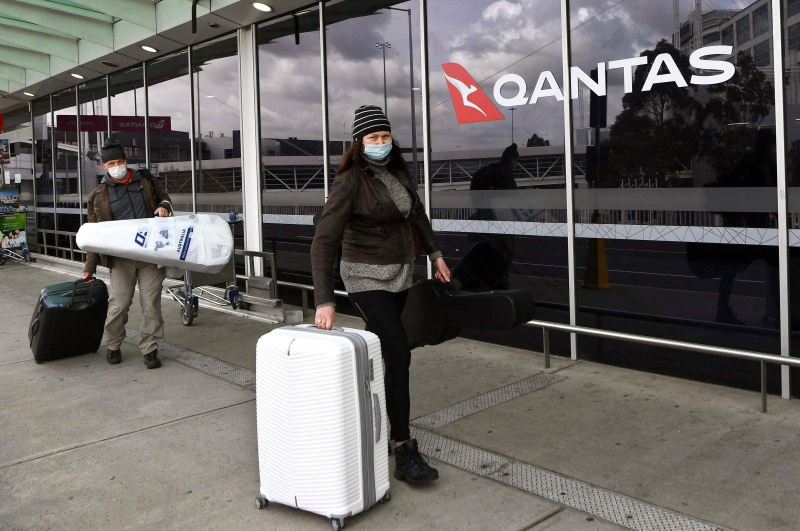 Travelers arrive at a deserted Qantas terminal at Melbourne Airport, Melbourne, Australia, Aug. 26, 2021. (AFP Photo)
