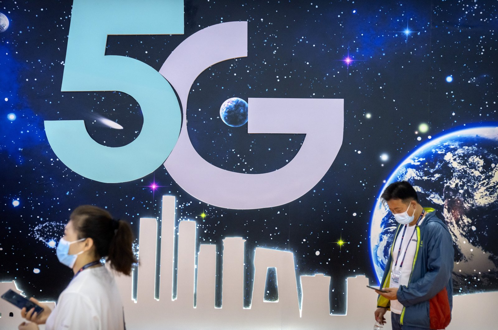 Attendees walk past a booth advertising 5G telecommunications services at the PT Expo in Beijing, China, Sept. 28, 2021. (AP Photo)