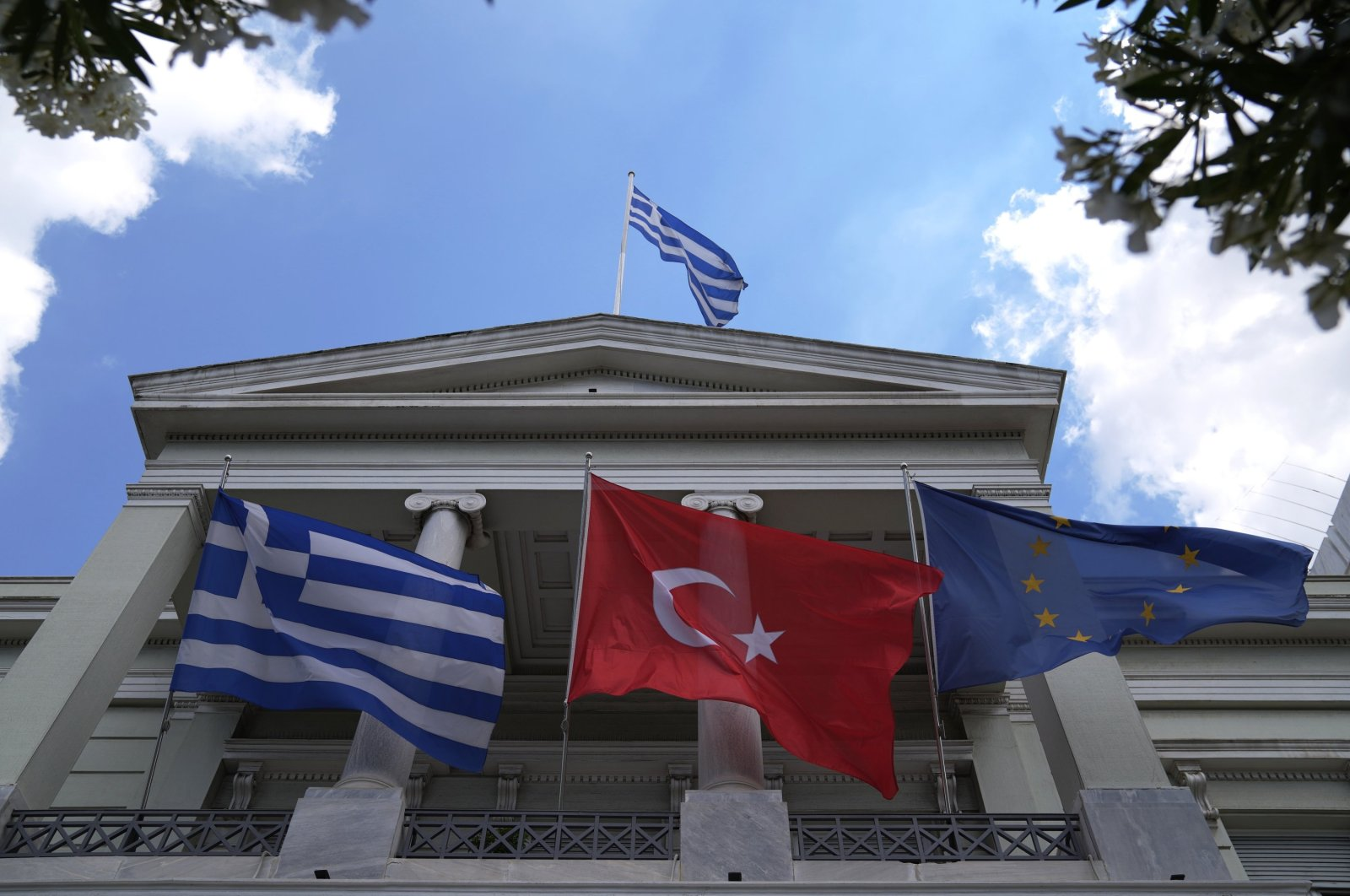 Greek (L) Turkish (M) and European Union flags flutter on the Foreign Ministry house before a meeting of Greek Foreign Minister Nikos Dendias and his Turkish counterpart Mevlüt Çavuşoğlu in Athens, Greece, May 31, 2021. (AP File Photo)