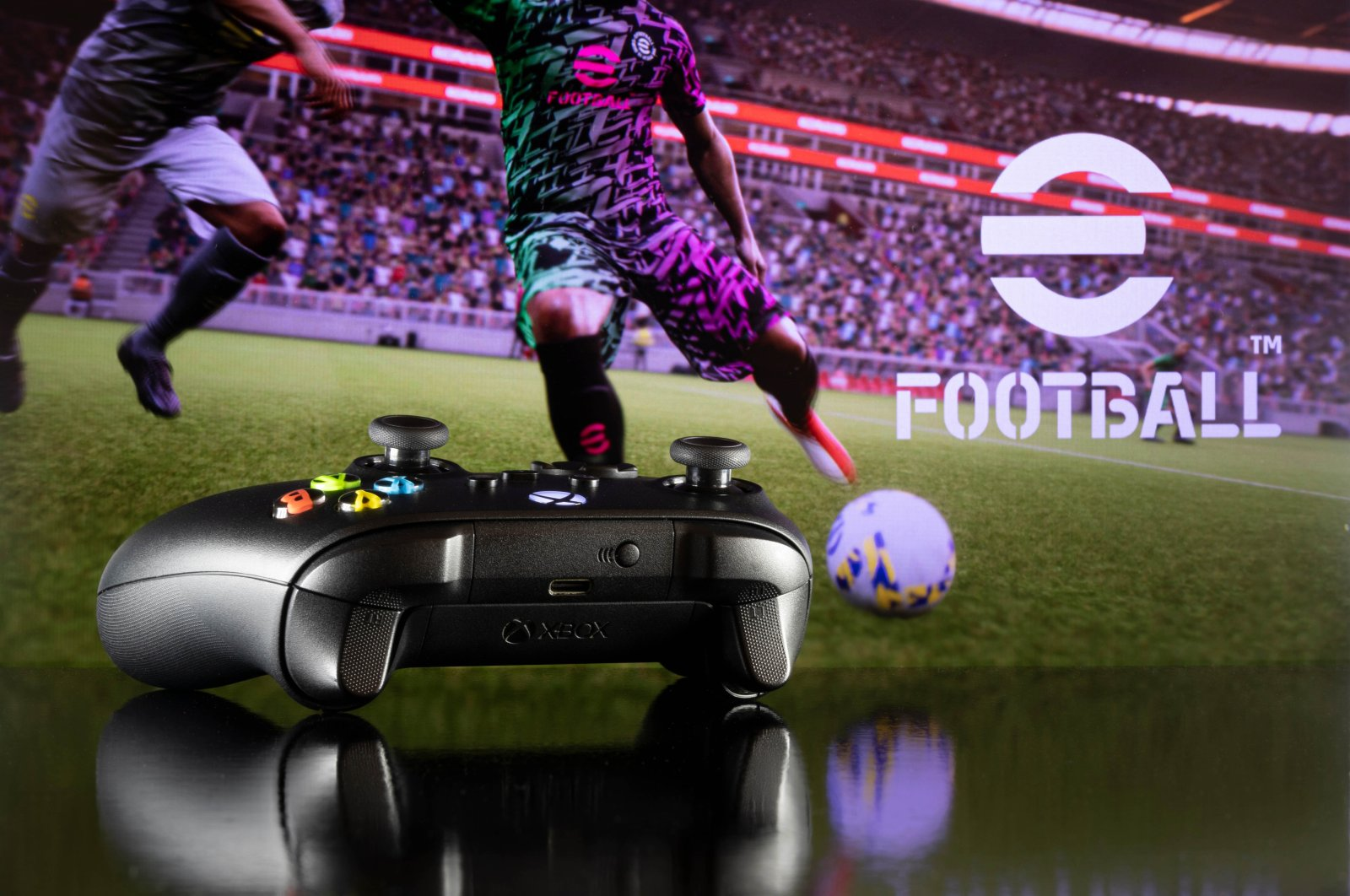 """An Xbox controller stands on a table with Konami's """"eFootball"""" game visible in the background, Sao Paulo, Brazil, July 26, 2021. (Shutterstock Photo)"""
