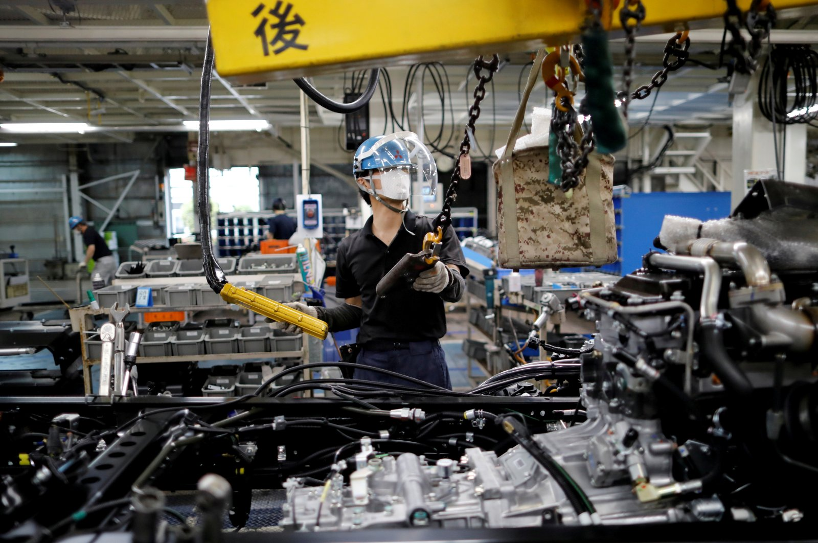 An employee wearing a protective face mask and face guard works on the automobile assembly line at Kawasaki factory of Mitsubishi Fuso Truck and Bus Corp, owned by Germany-based Daimler AG, in Kawasaki, south of Tokyo, Japan, May 18, 2020. (Reuters Photo)