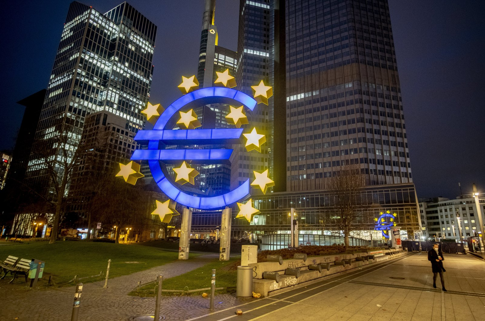 In this file photo, a man walks past the Euro sculpture in Frankfurt, Germany, March 11, 2021. (AP Photo)