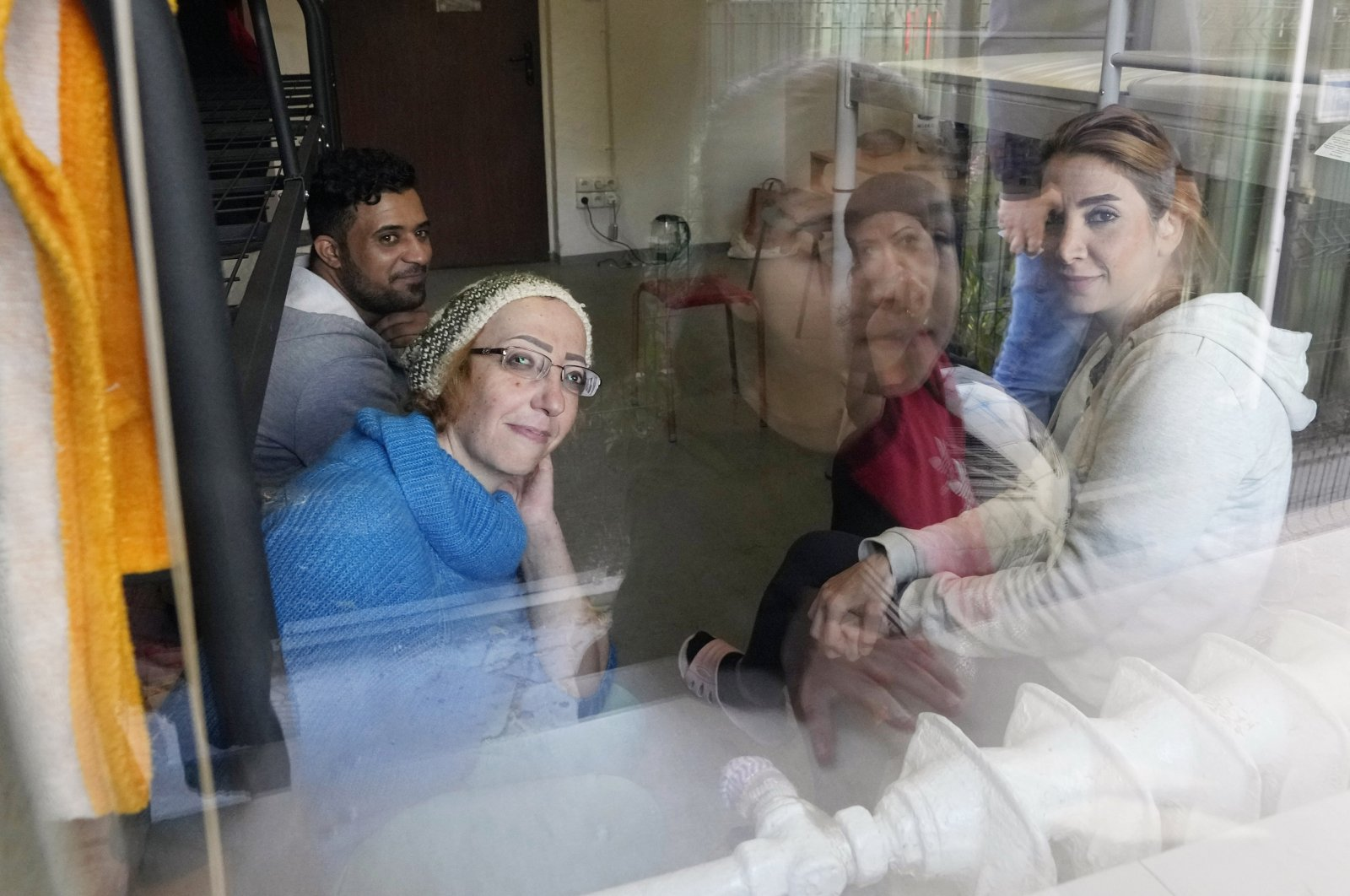 Boshra al-Moallem (foreground L), looks out of the window as she sits in a room with her two sisters and brother-in-law at a refugee center in Bialystok, Poland, Sept. 29, 2021. (AP Photo)