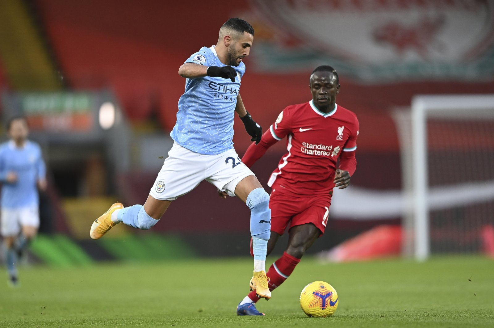 Manchester City's Riyad Mahrez (L) drives the ball past Liverpool's Sadio Mane in a Premier League match at the Anfield, Liverpool, England, Feb. 7, 2021. (AP Photo)