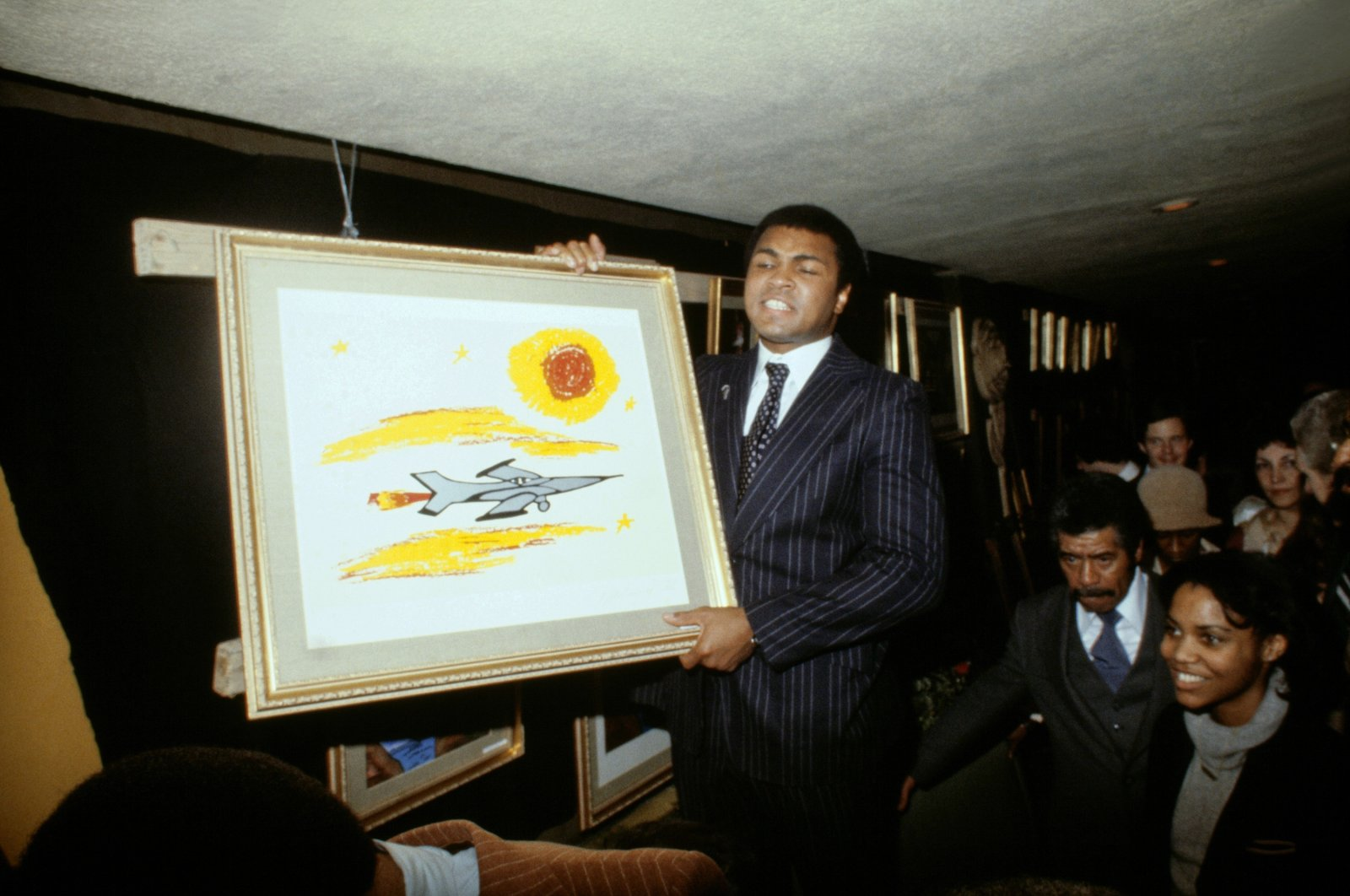 Muhammad Ali poses with a painting in 1960. (Getty Images)